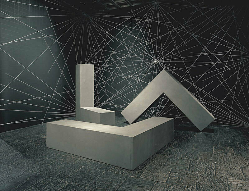 An installation of 3 large L-shaped blocks in a gallery.