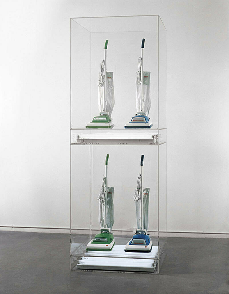 An installation of 4 vacuum cleaners in a glass case.