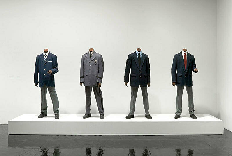 A sculpture of four people without heads wearing different suits.