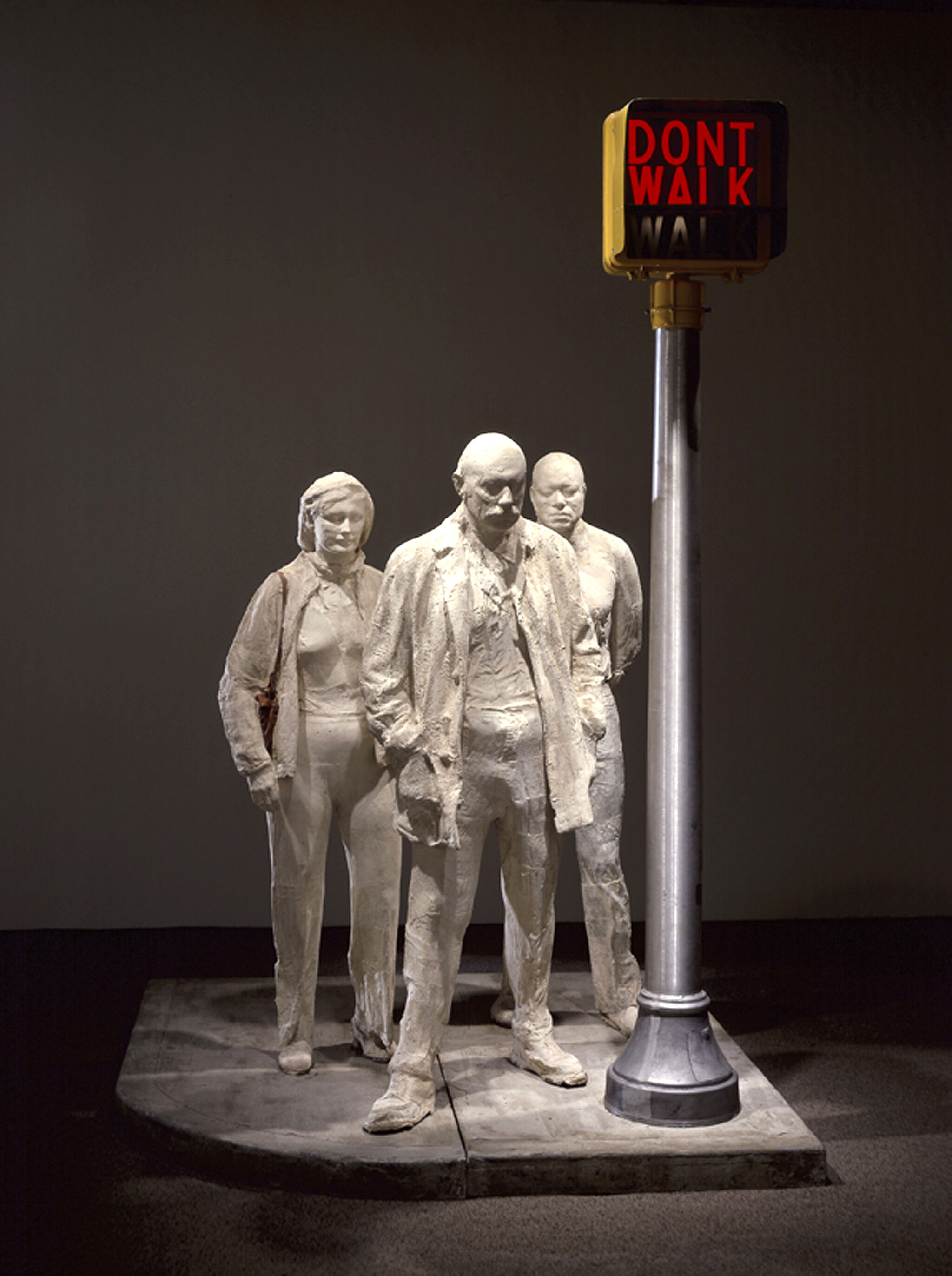 A sculpture of three people standing at a crosswalk sign.