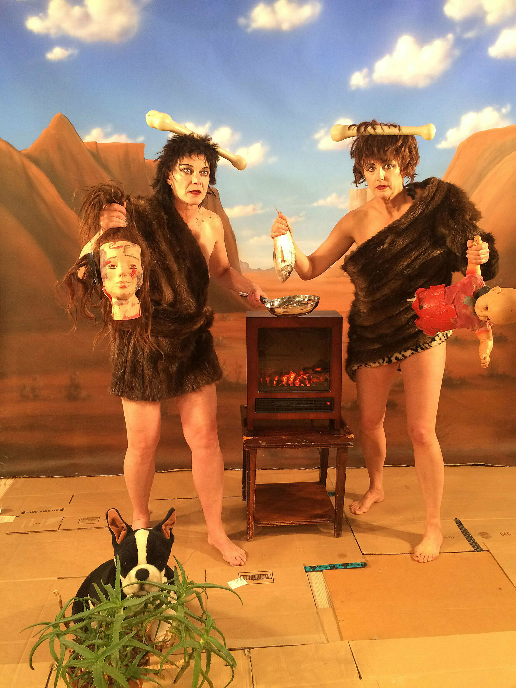 Two women dressed as neanderthals, on a stage set.