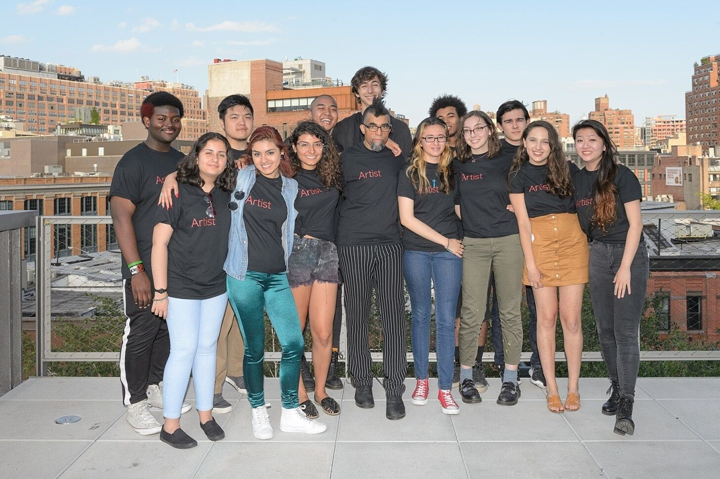 A group portrait with artist Dread Scott on an outdoor terrace at the museum.
