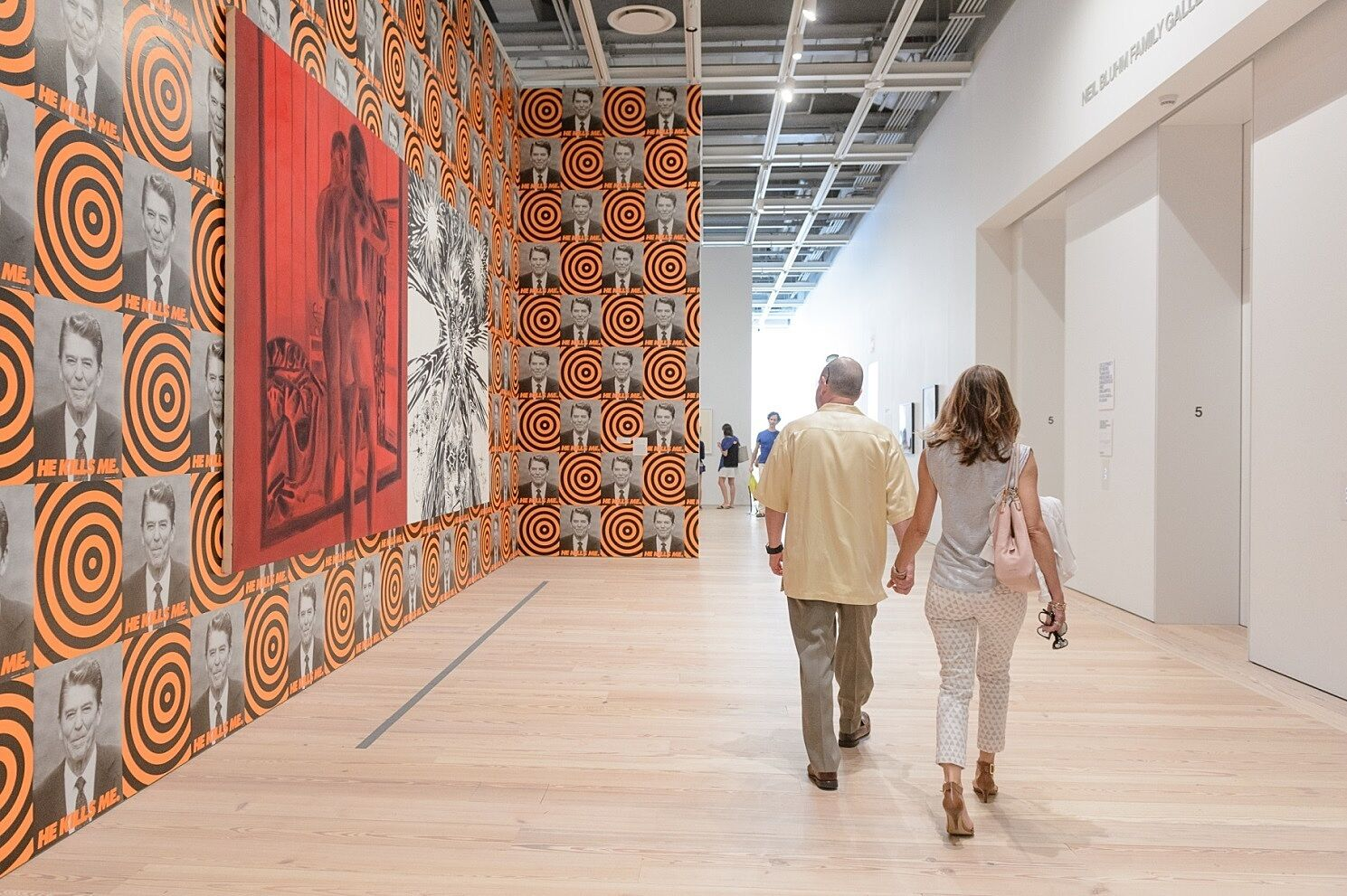 Two adults walks through a gallery during the event.