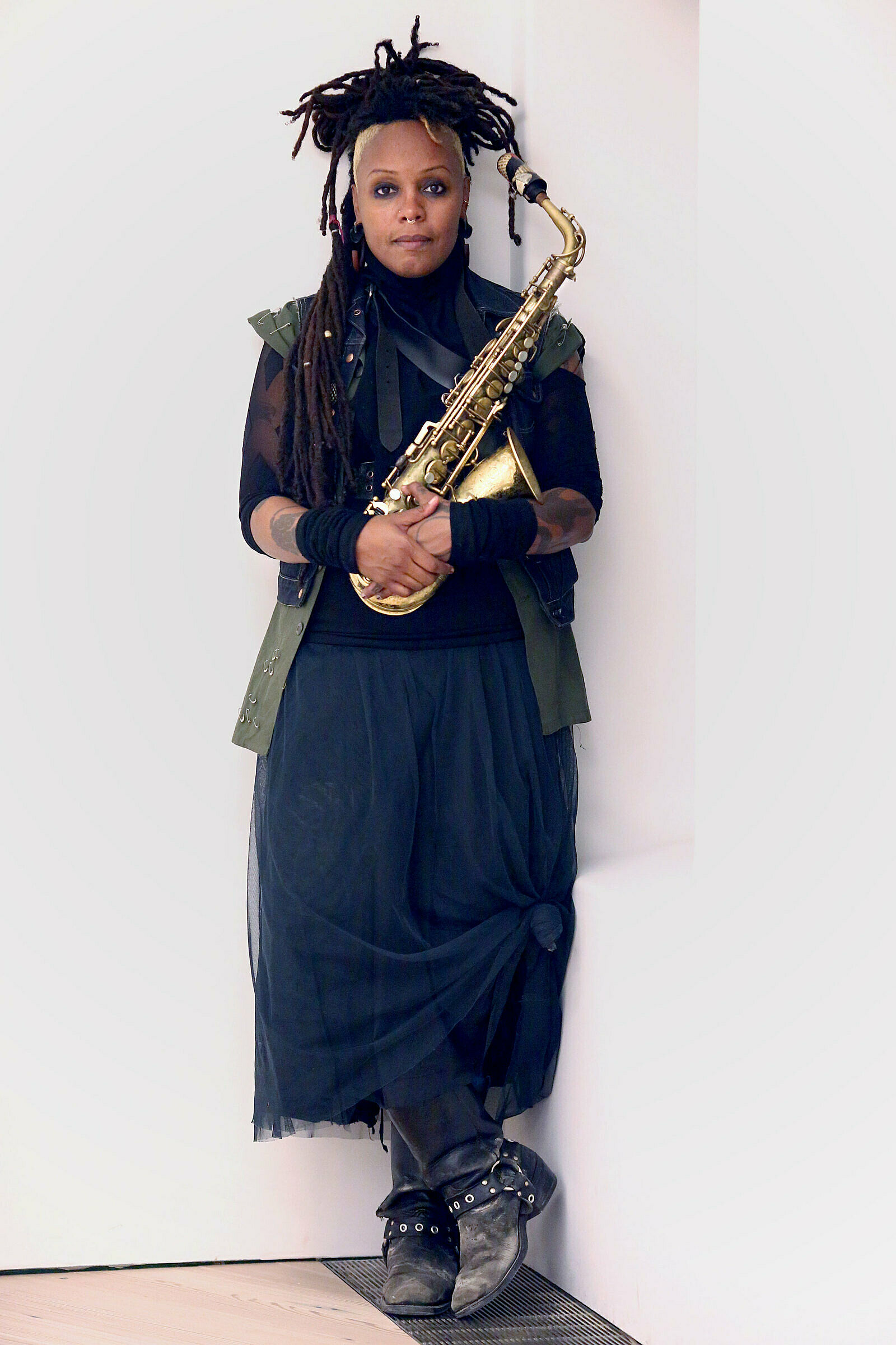 Matana Roberts leans against a wall with a saxophone.