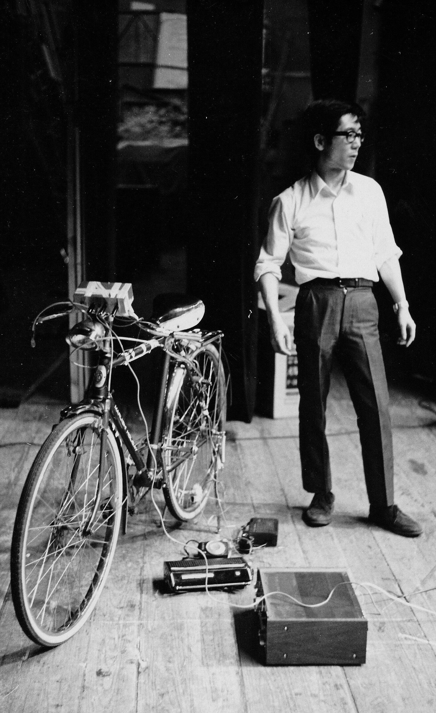 The artist stands with a bicycle which is wired to electrical contraptions
