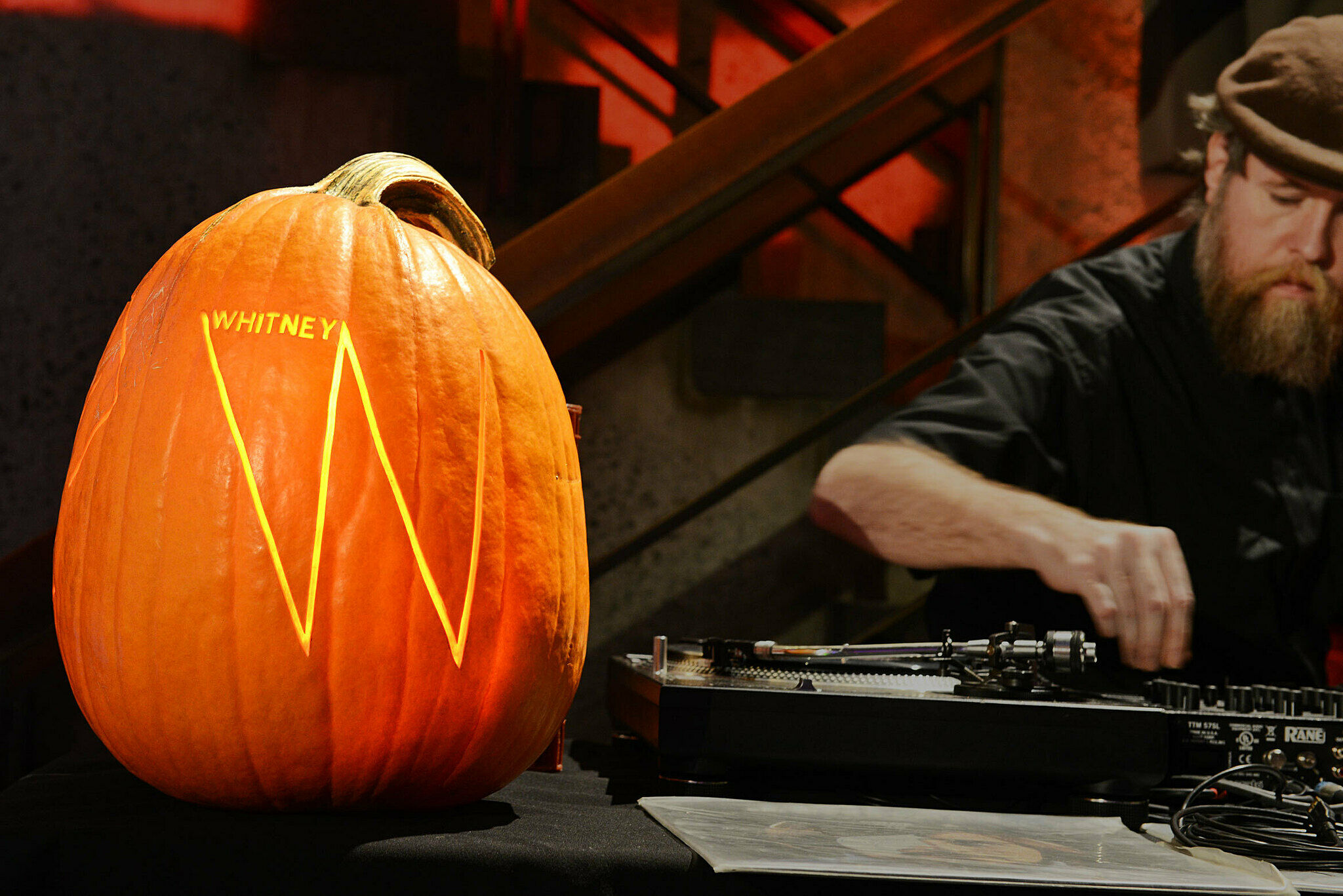 Pumpkin with whitney logo on it next to DJ playing records.