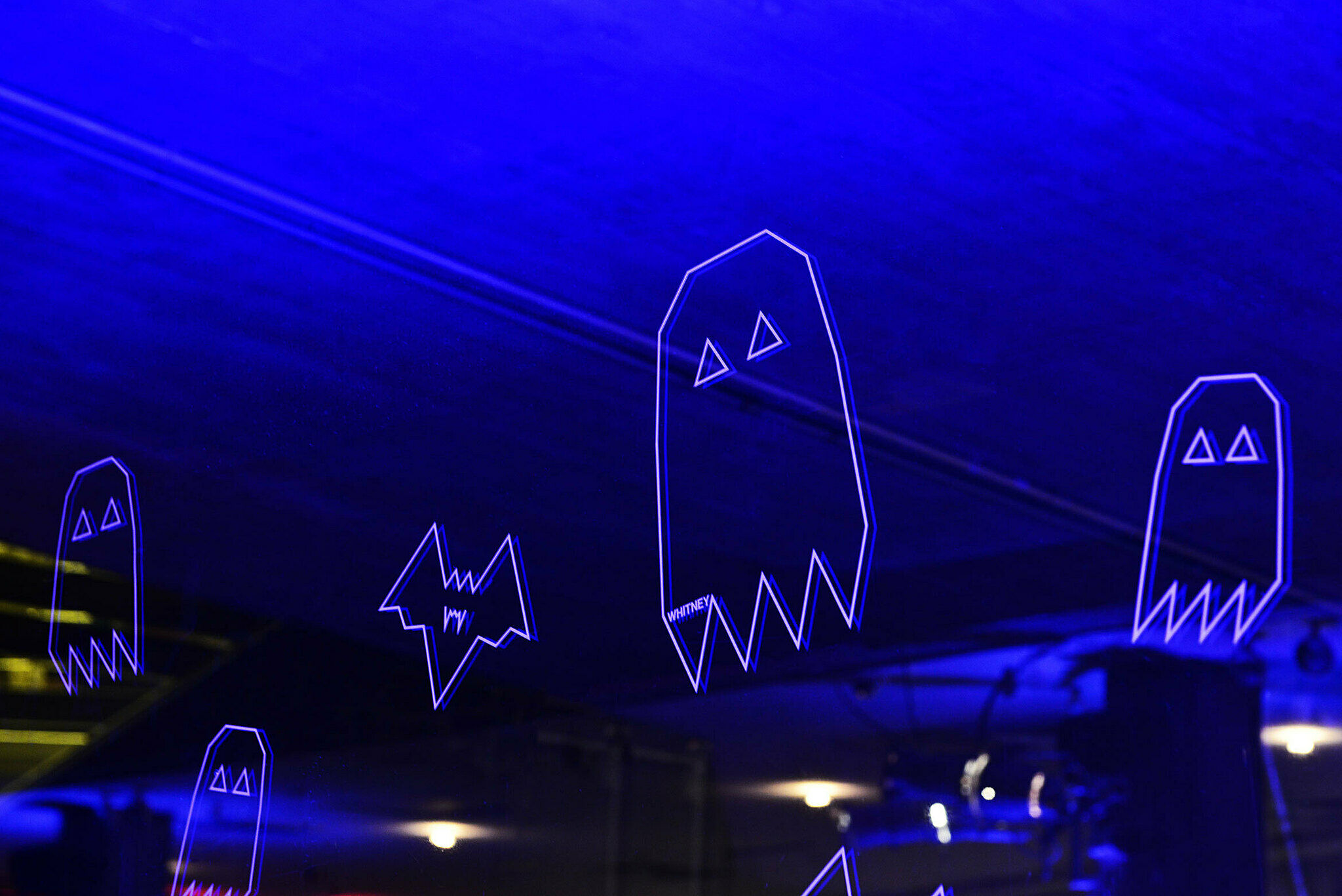 Neon purple outlined ghosts in window.