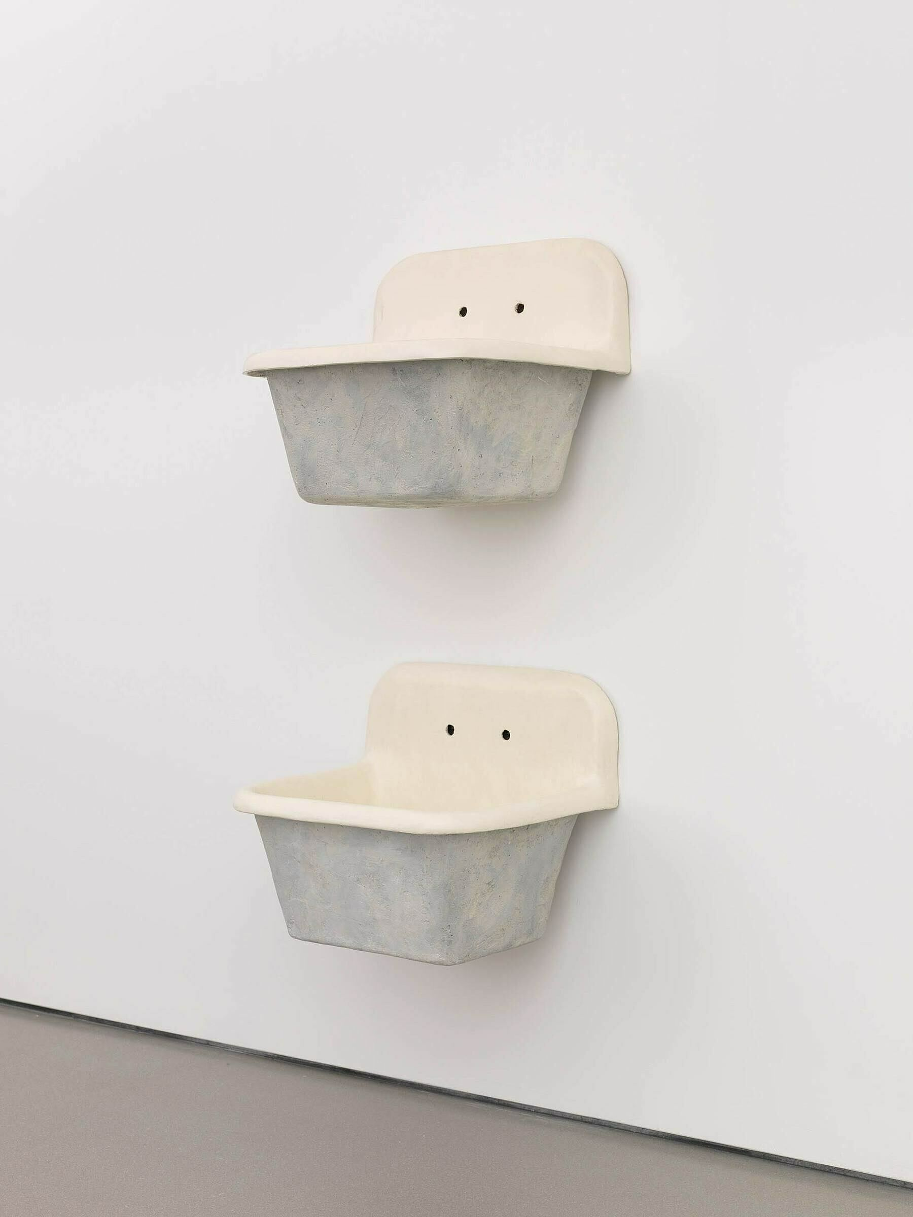 Two sculptures of sink basins attached to a wall.