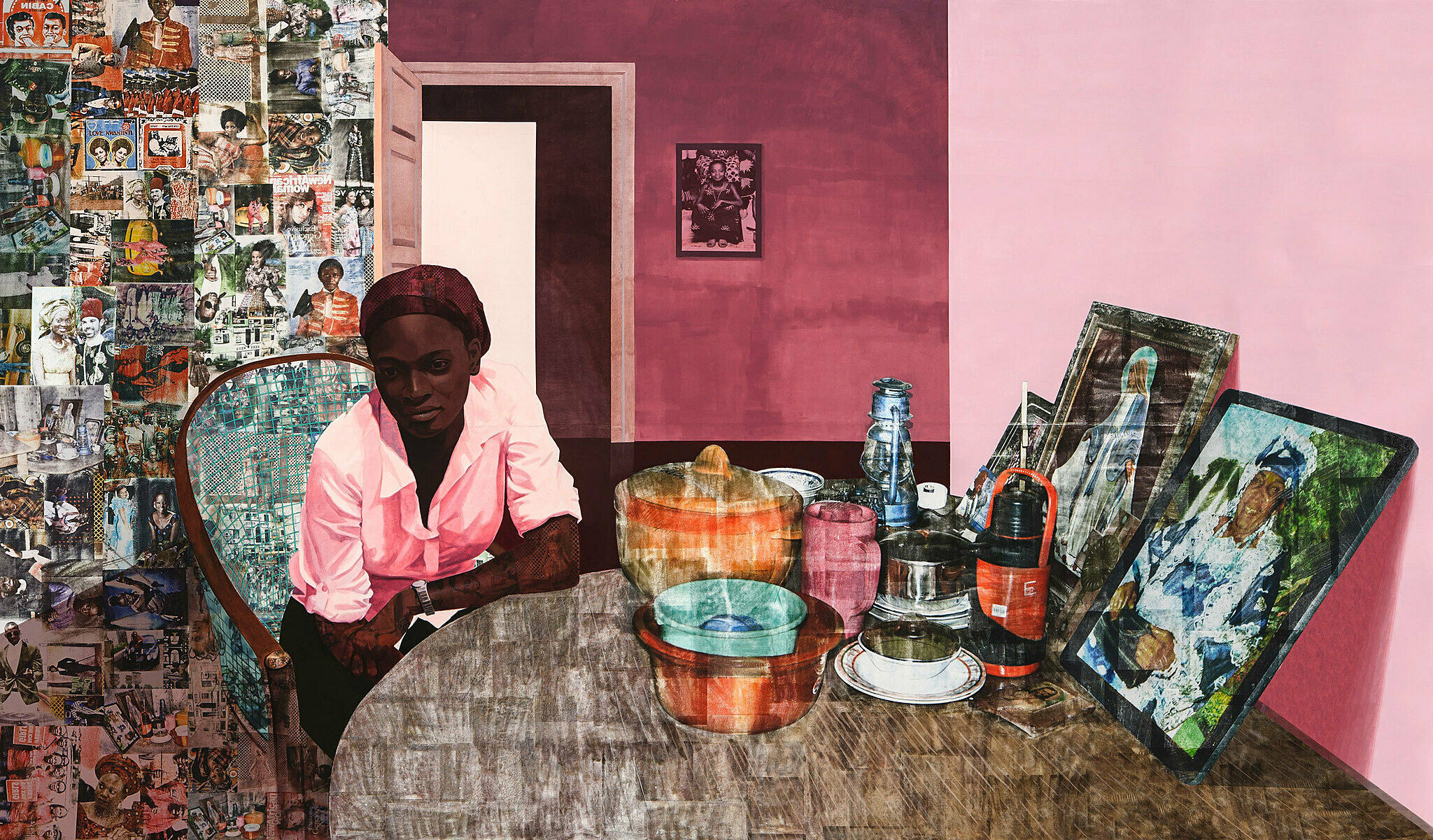 A collaged portrait by Njideka Crosby. A woman sits at a table with photographs behind her.