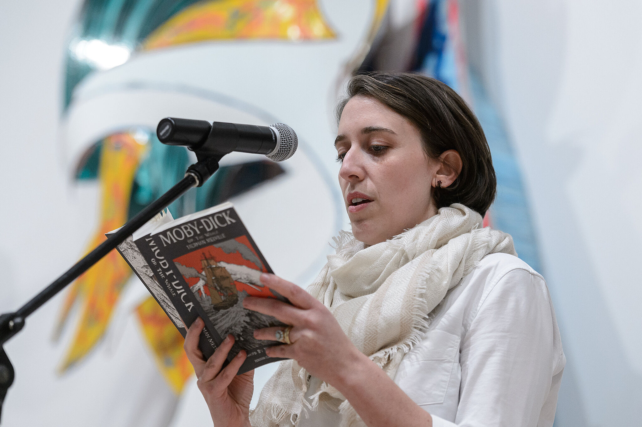 Woman reading a book with microphone.