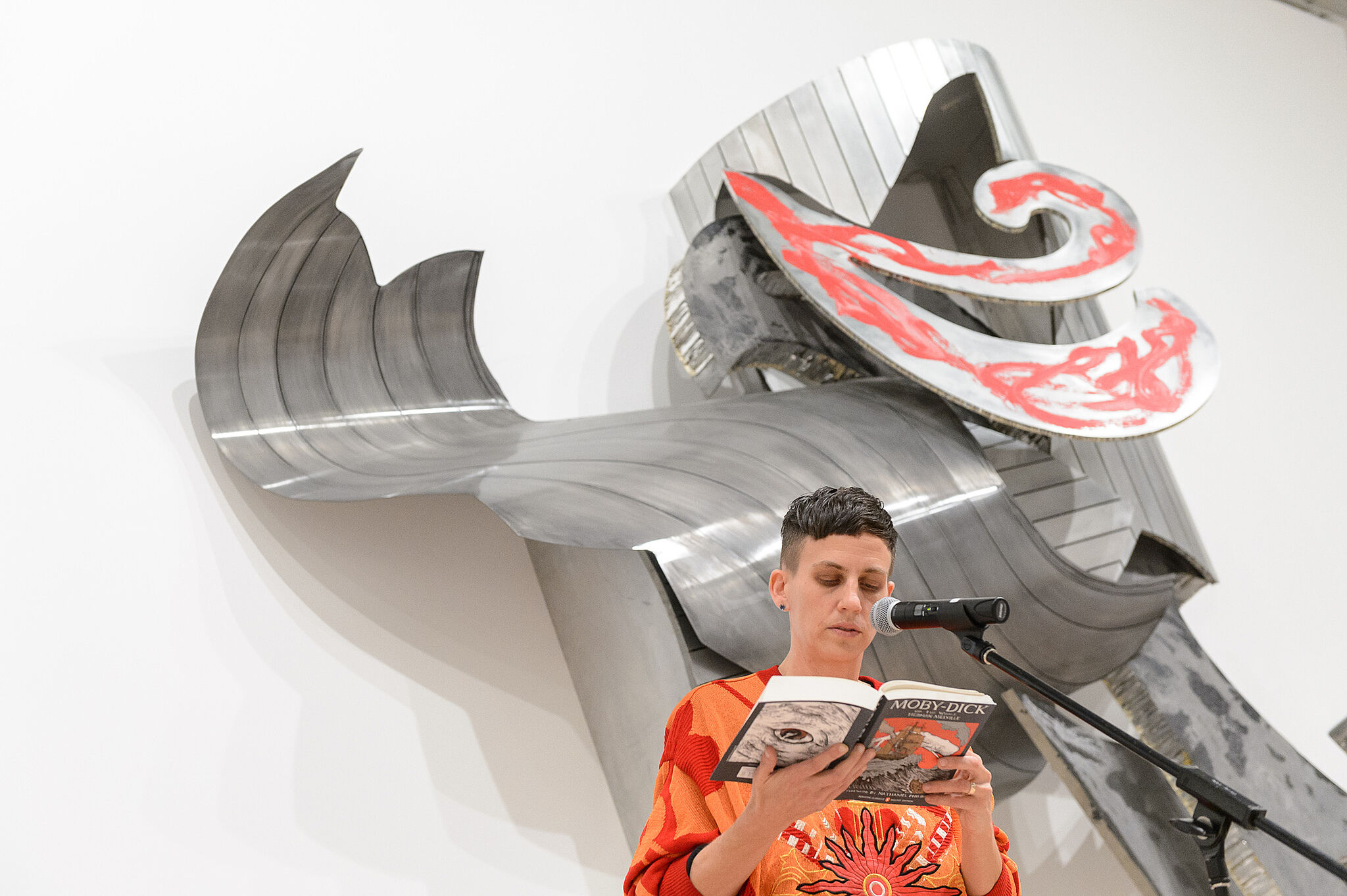 Woman reading in front of installation.