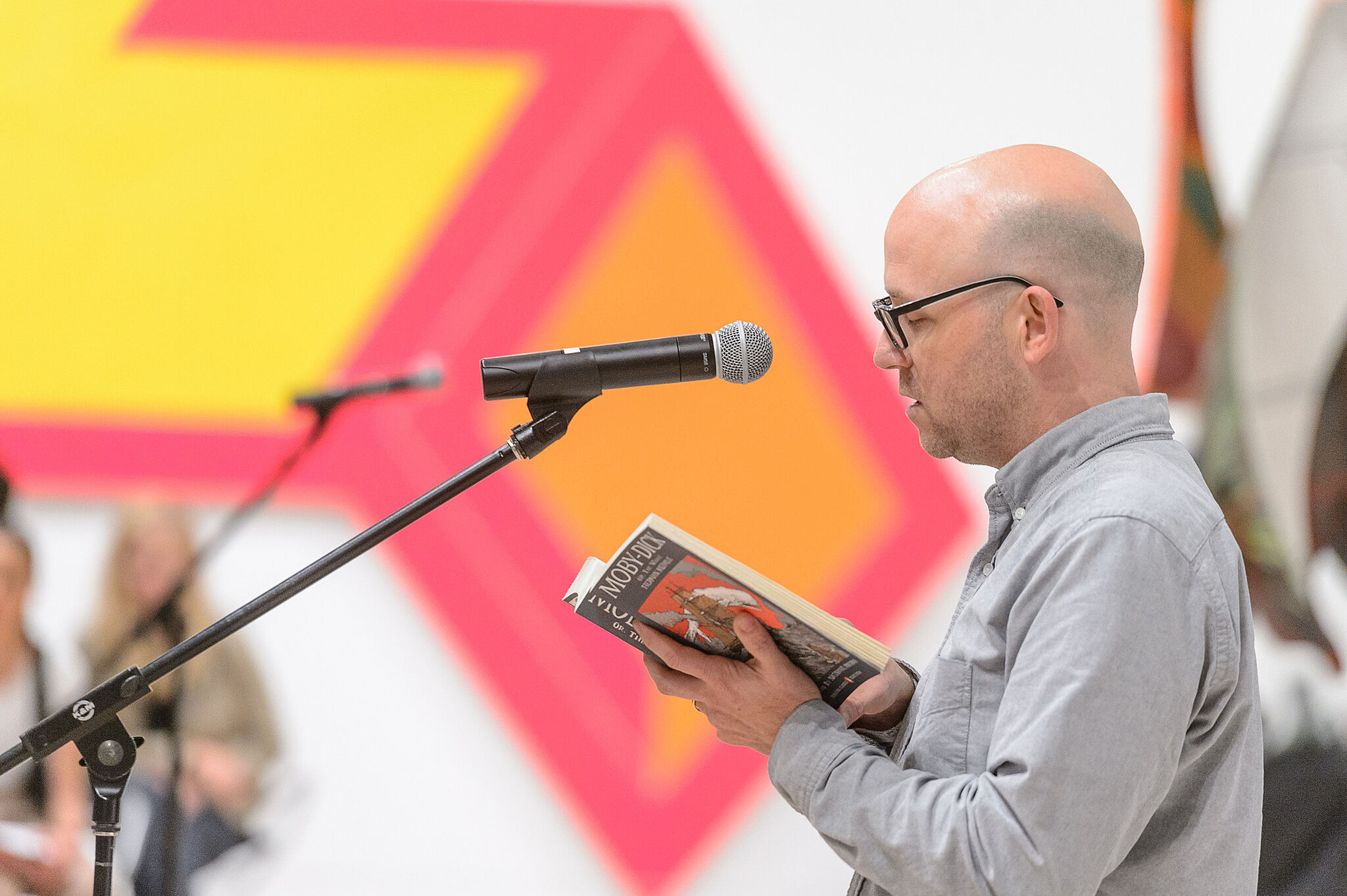 Man reading book to microphone.