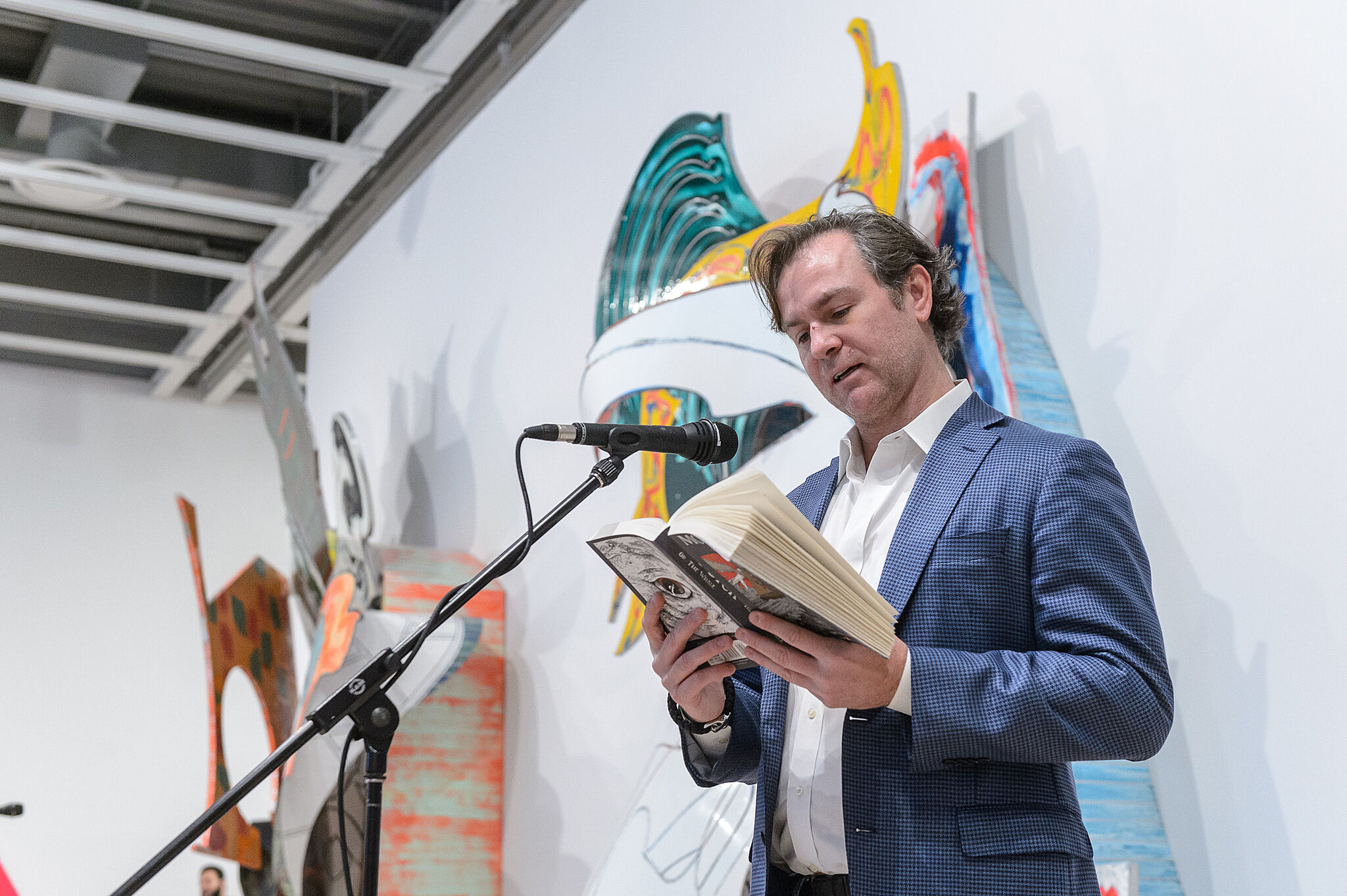 Man in suit reading from Moby Dick.