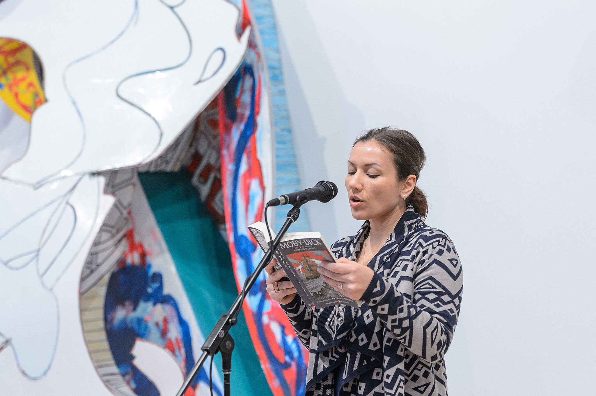Woman reading into a microphone.