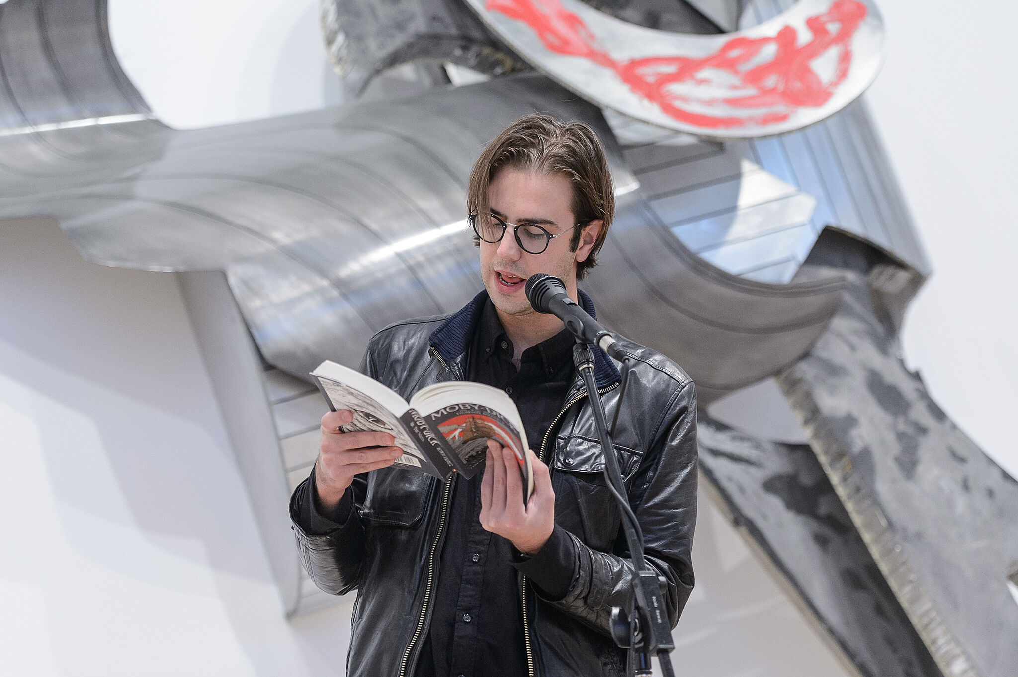 Man with a jacket reading from the book.