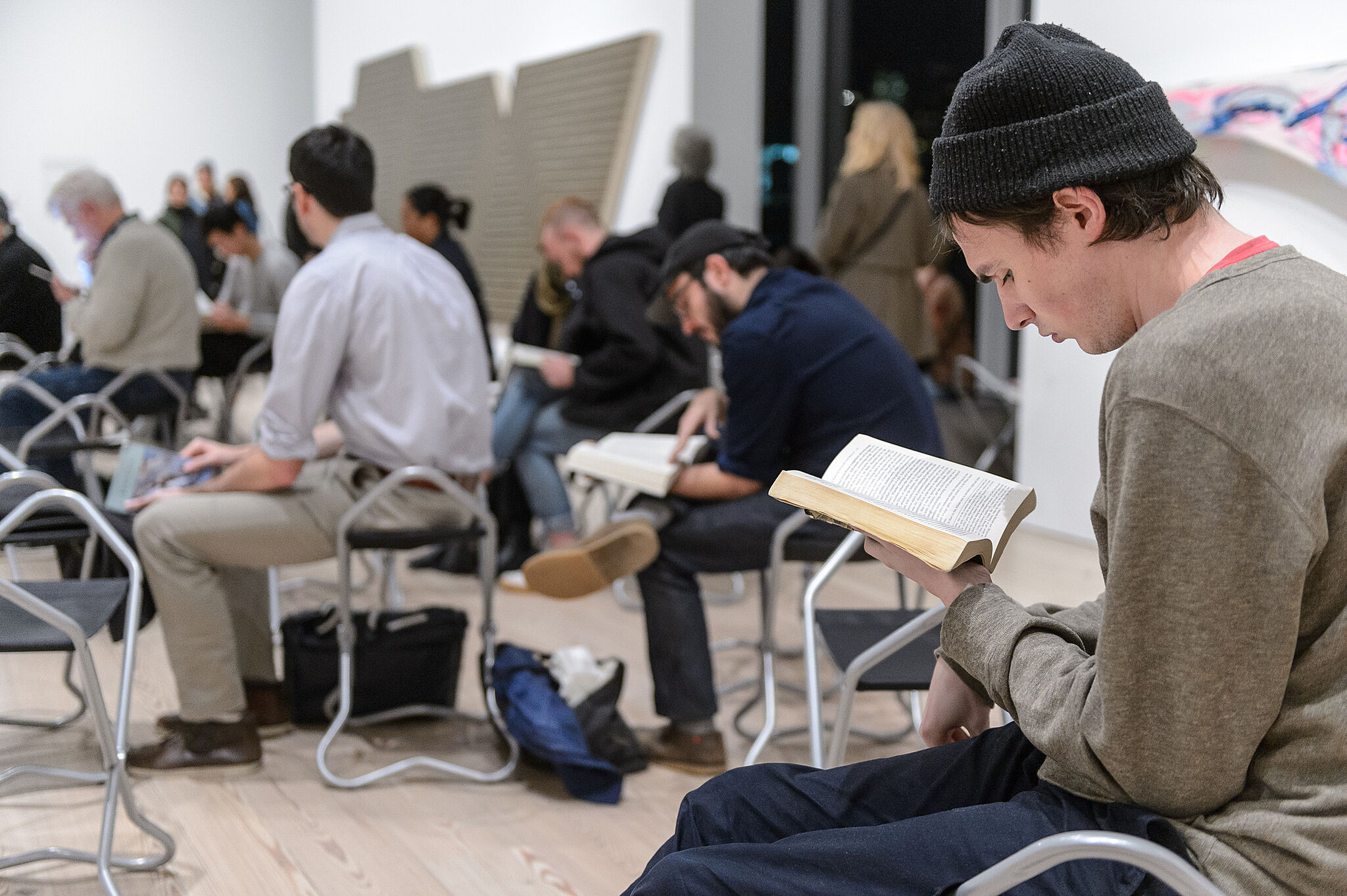 Men reading in an audience.