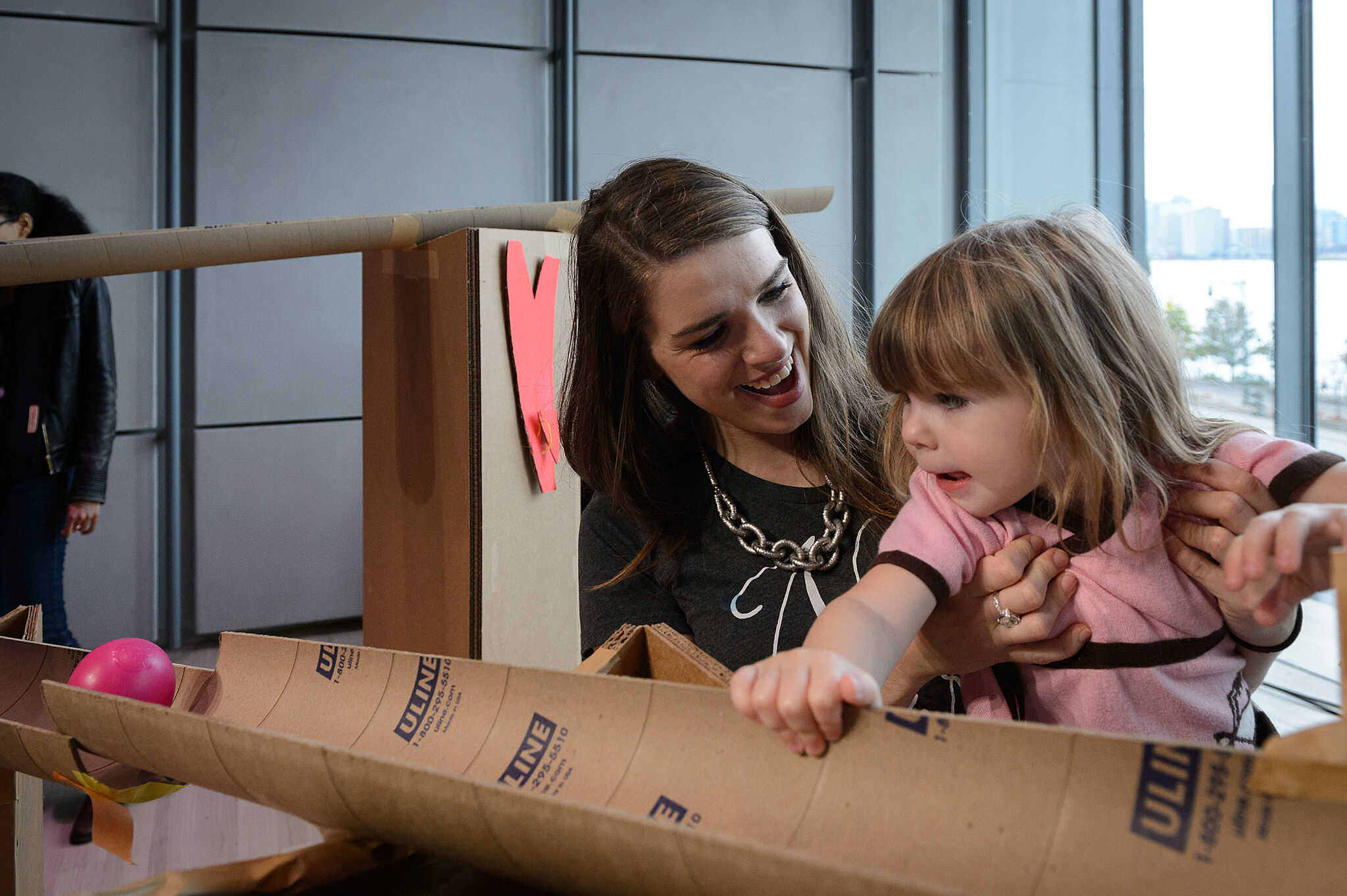 Mother and daughter play in front of cardboard.