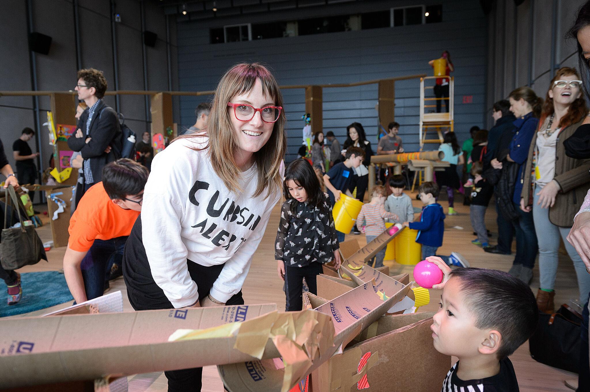 Artist helps children with marble run.