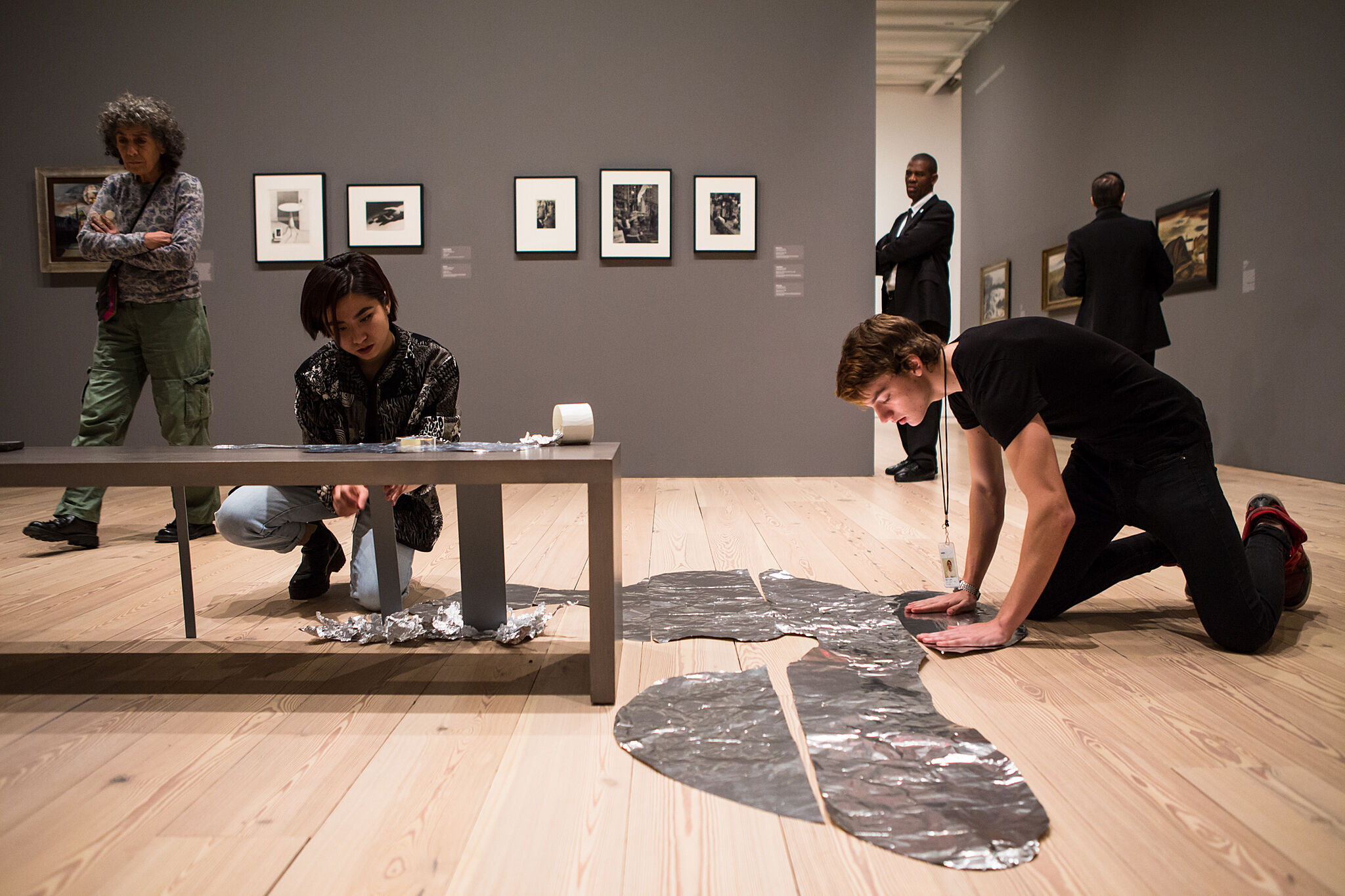 Students work on a bench in a museum gallery to build part of the installation.