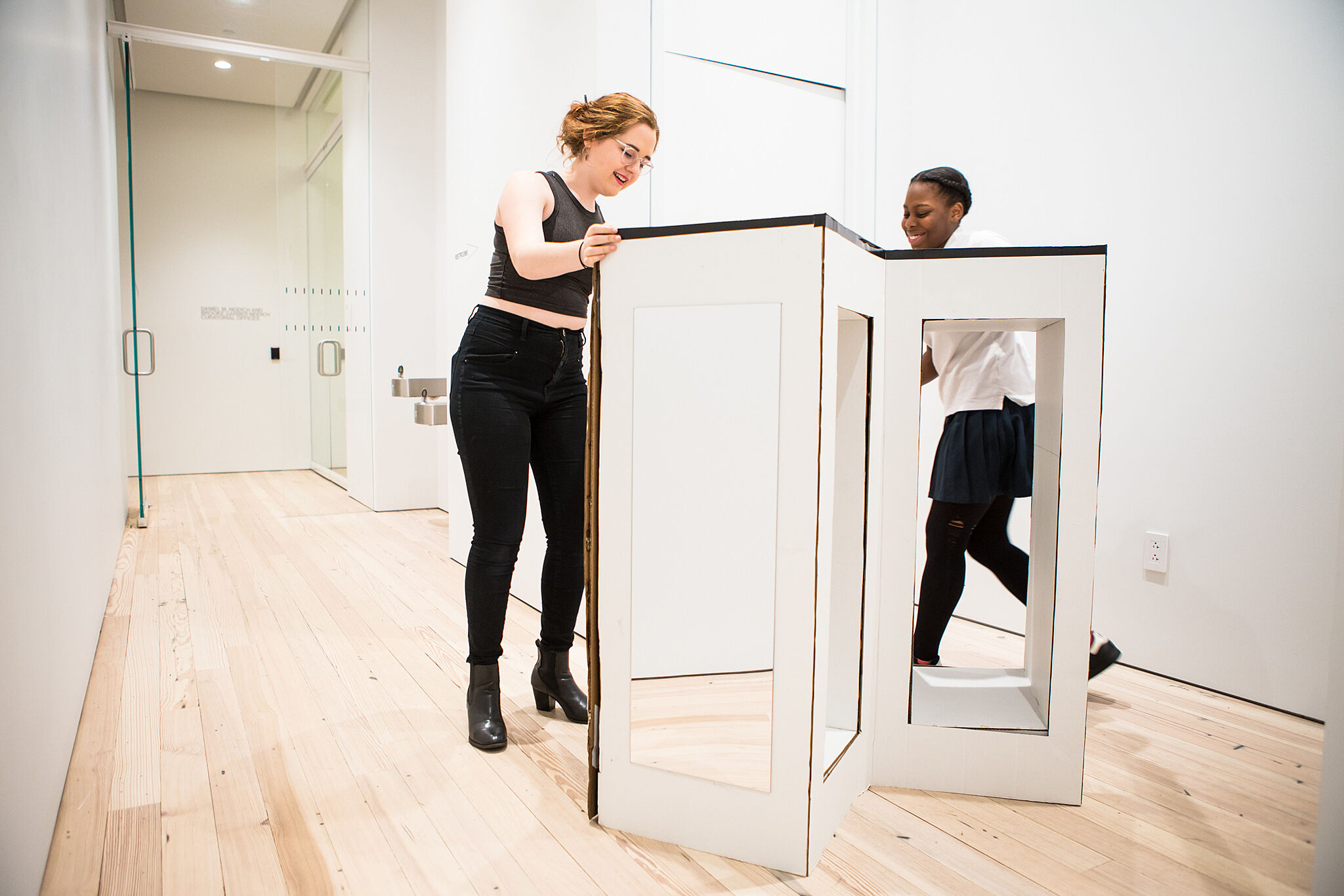 Two teens set up a mirror sculpture in museum space.