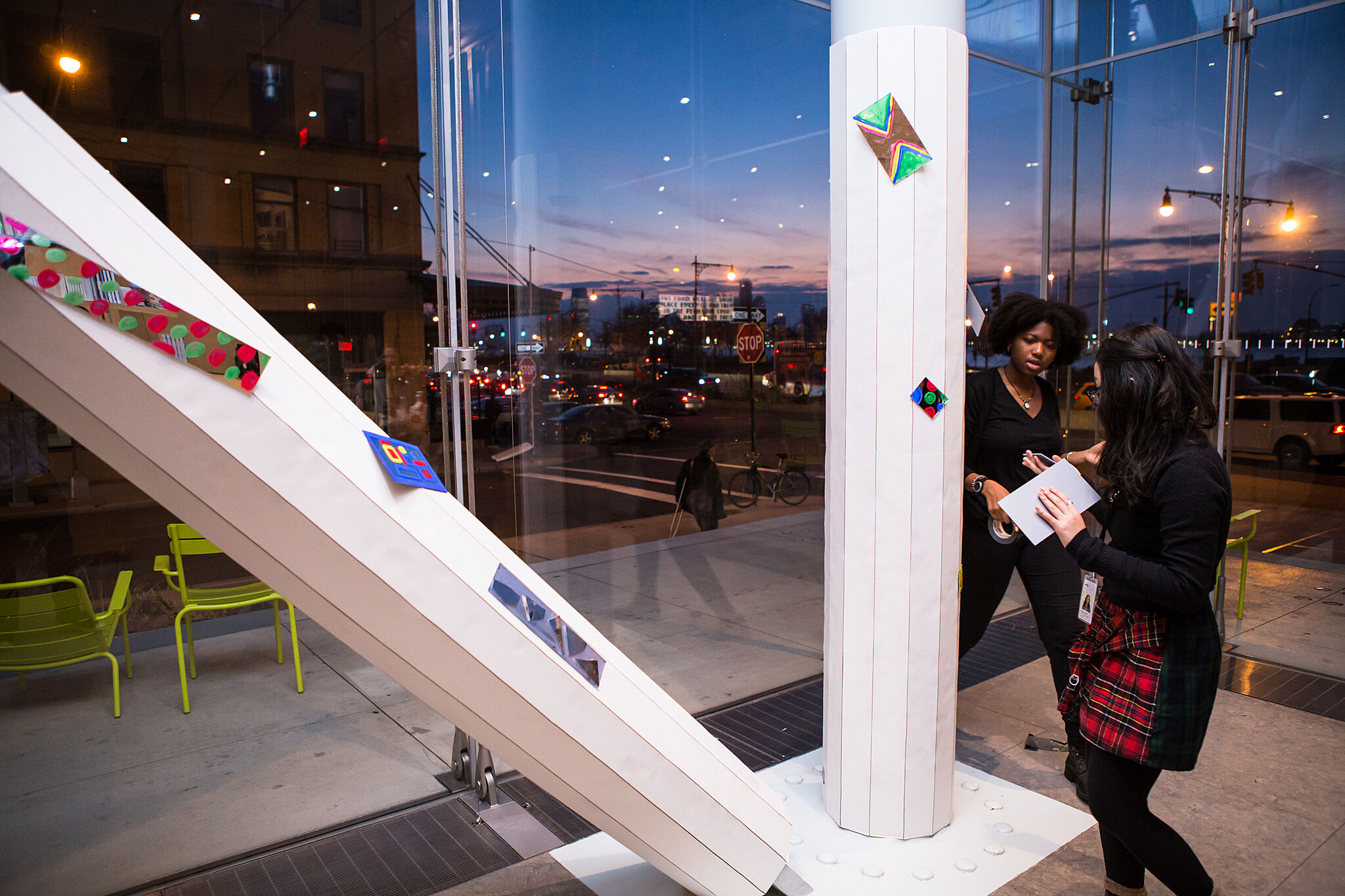 Two students put mirror art on white columns in the museum.
