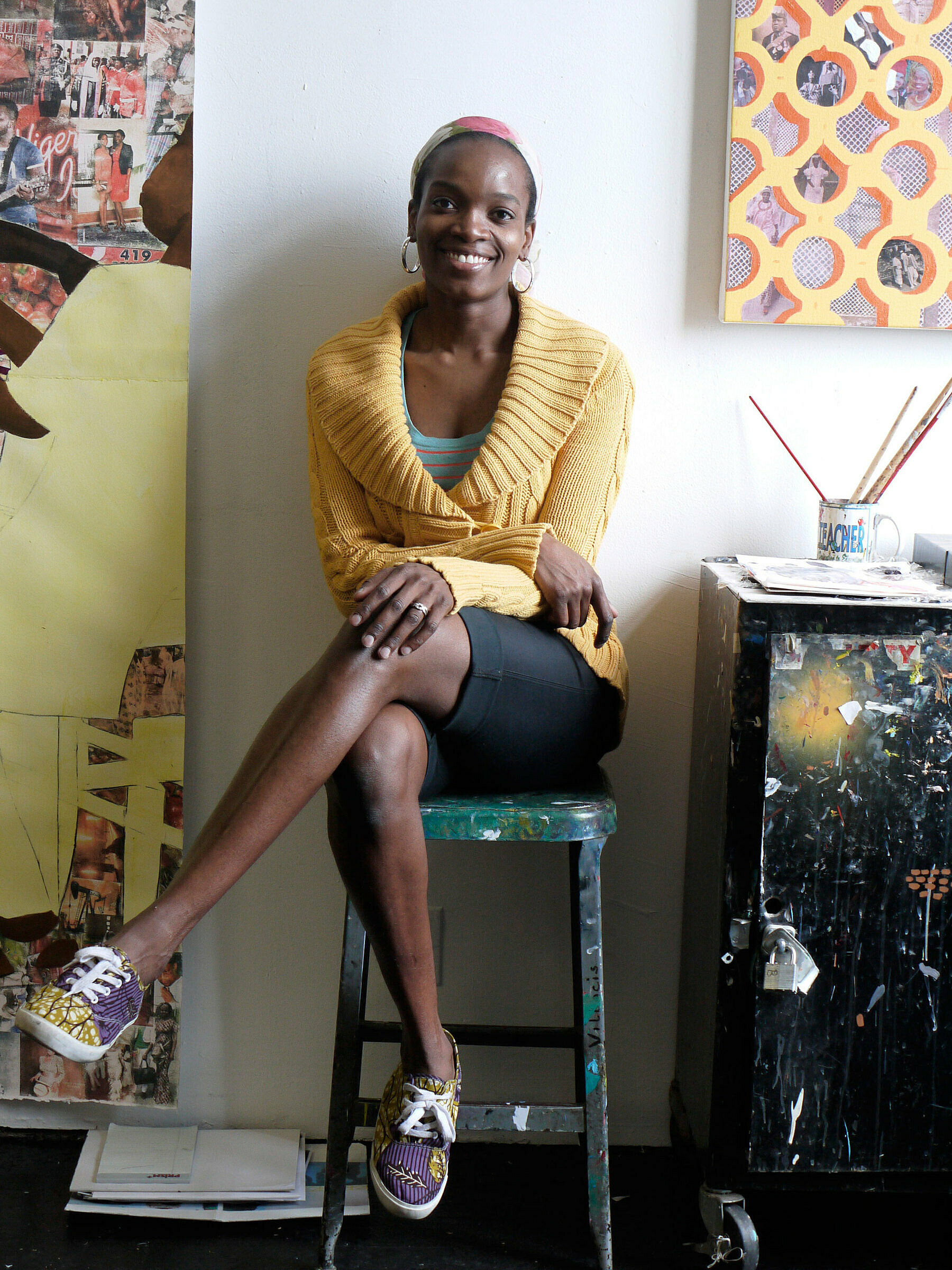 Artist Njideka Akunyili Crosby sits upon a stool in her studio. Two of the artists works are installed on the walls behind her