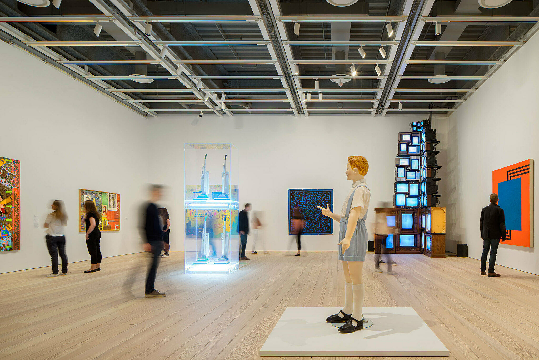 The Whitney's galleries. Sculpture and paintings fill the gallery populated by visitors