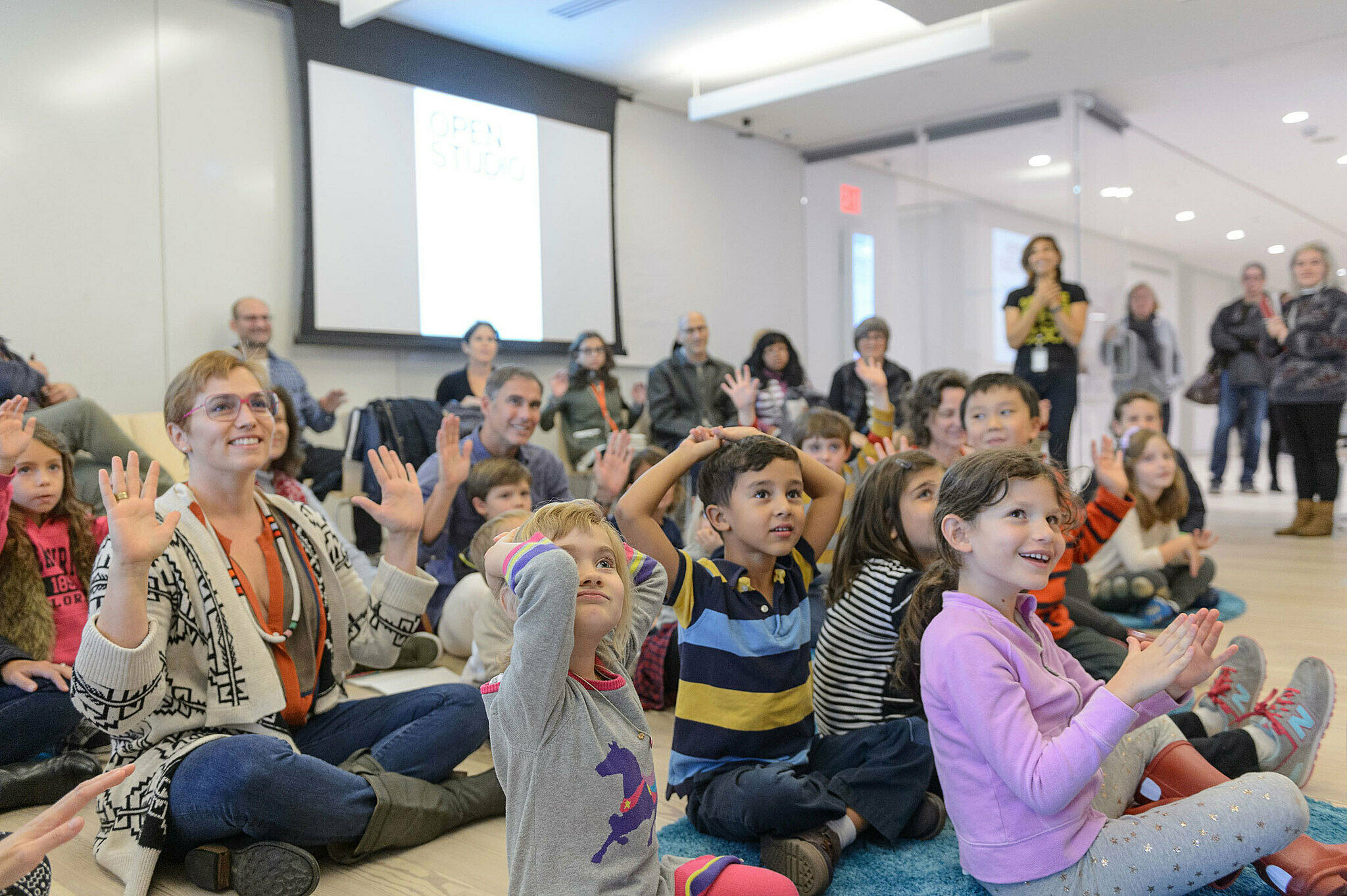 Families raise their hands in an Open Studio workshop led by artist Cooper-Moore.