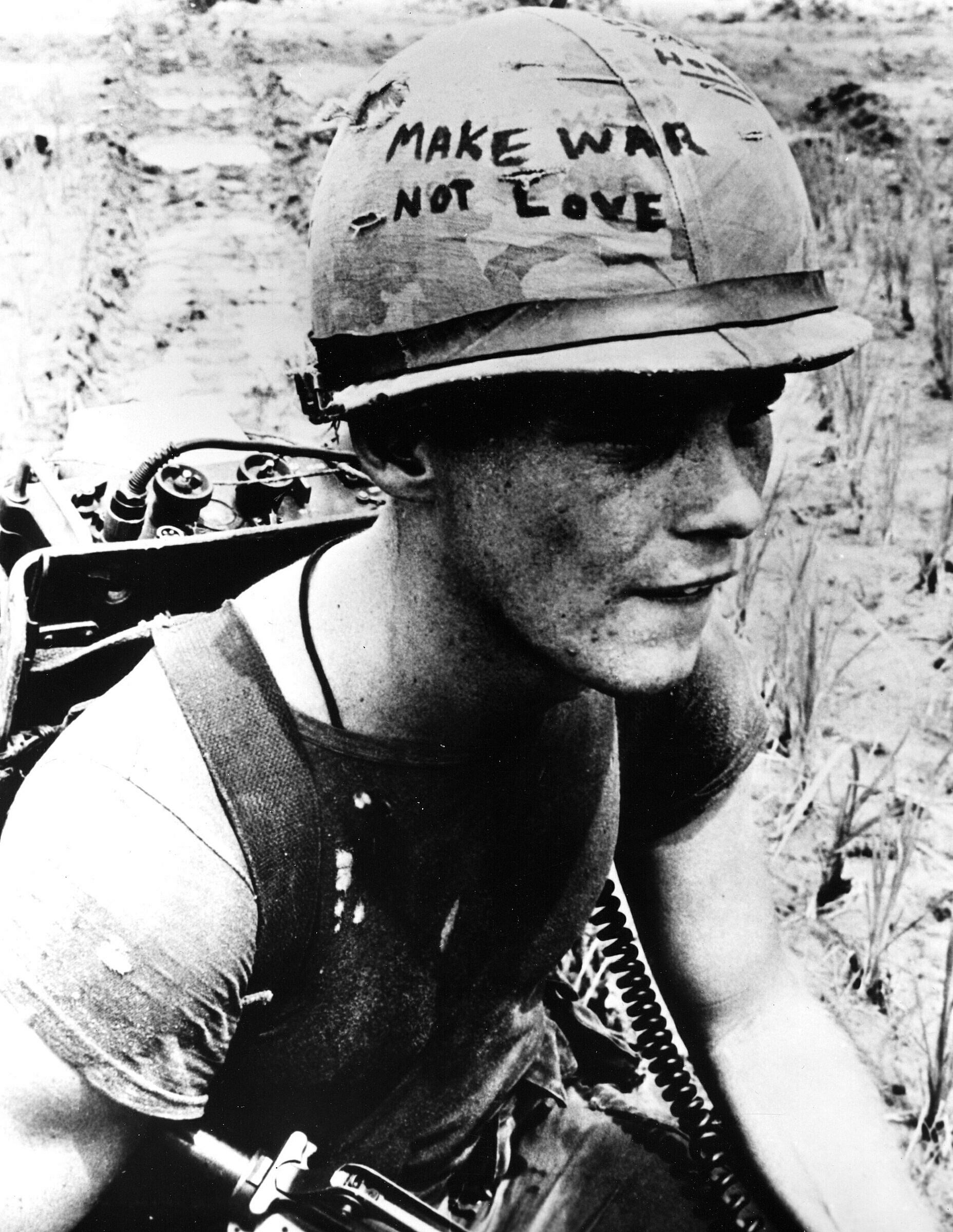 "A film still of a work by Emile de Antonio. An American soldier in Vietnam wears a helmet. ""Make love not war"" is written on the brim"