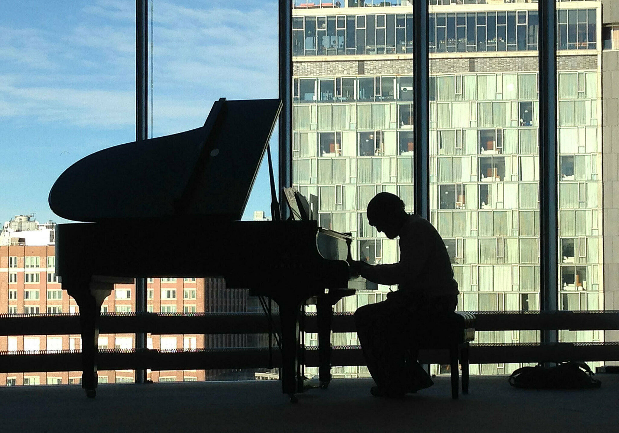 Cecil Taylor sitting at a baby grand piano.