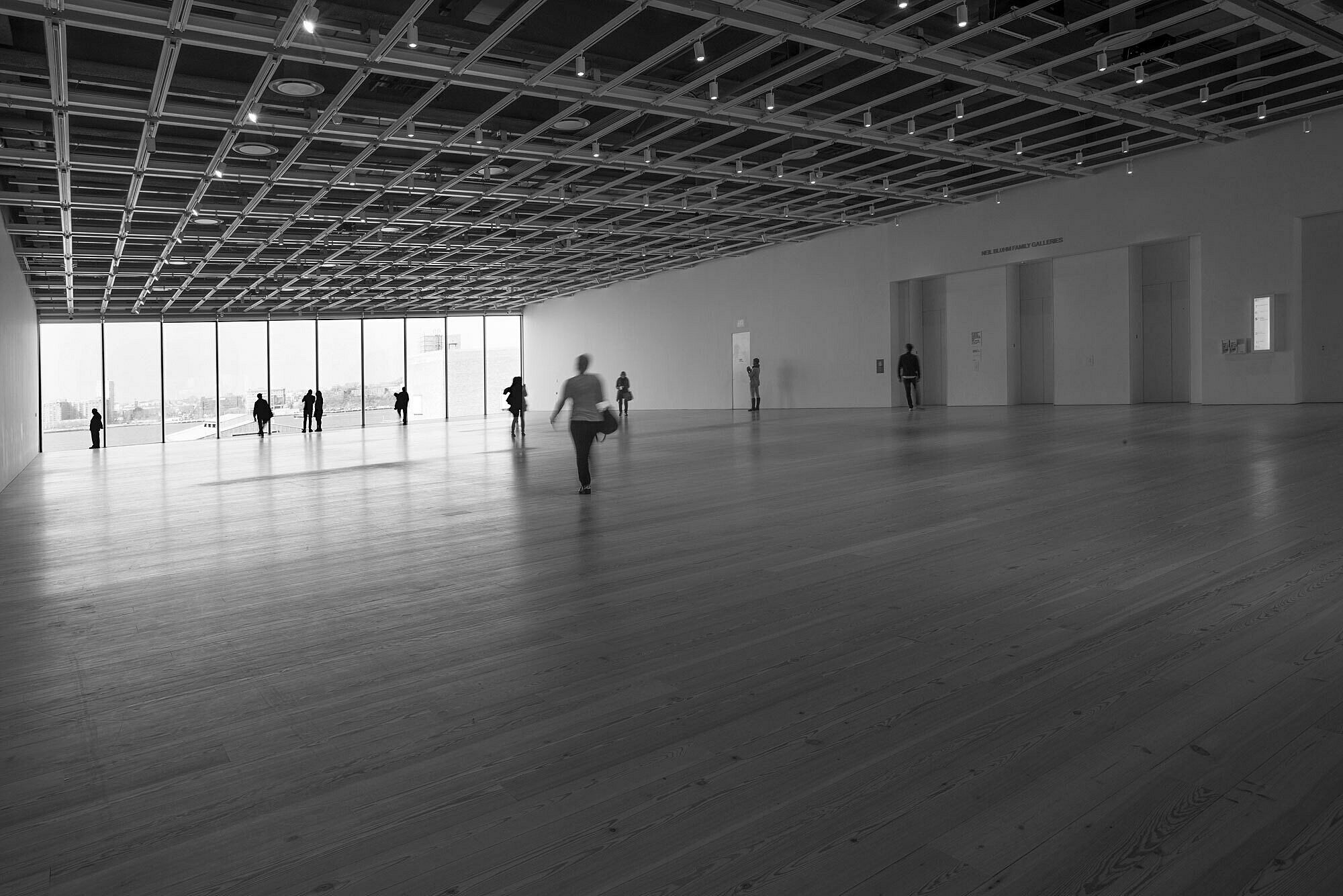 A lone figure stands in the fifth floor Whitney galleries in black and white.