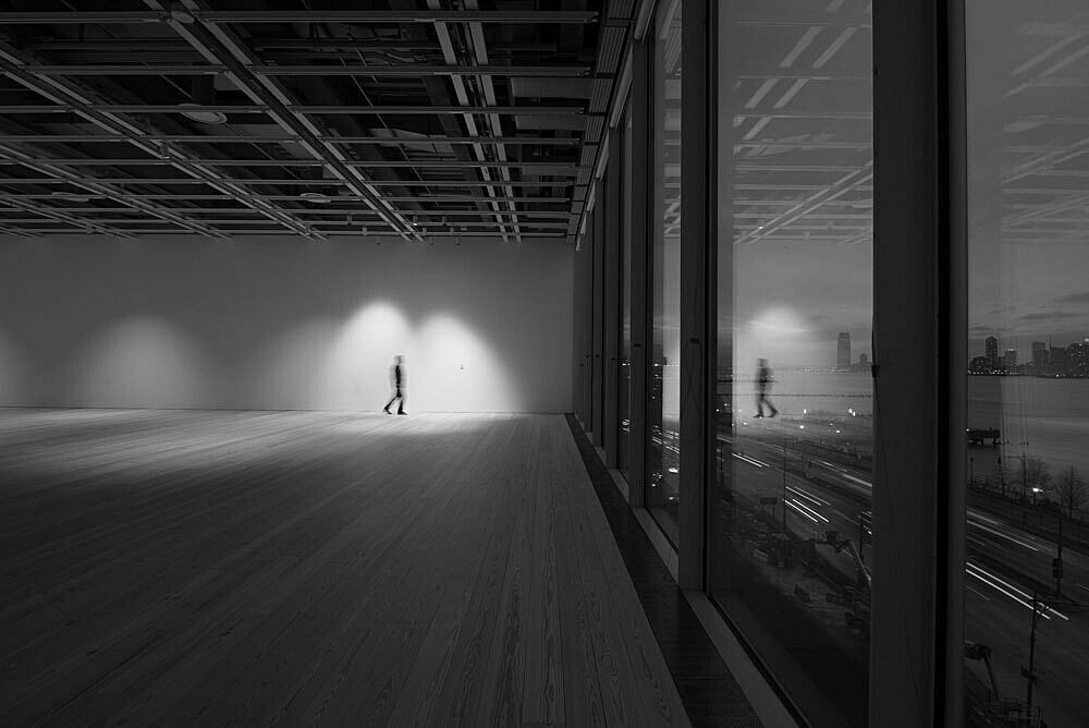 A lone figure stands in the empty fifth floor galleries of the Whitney Museum lit at night