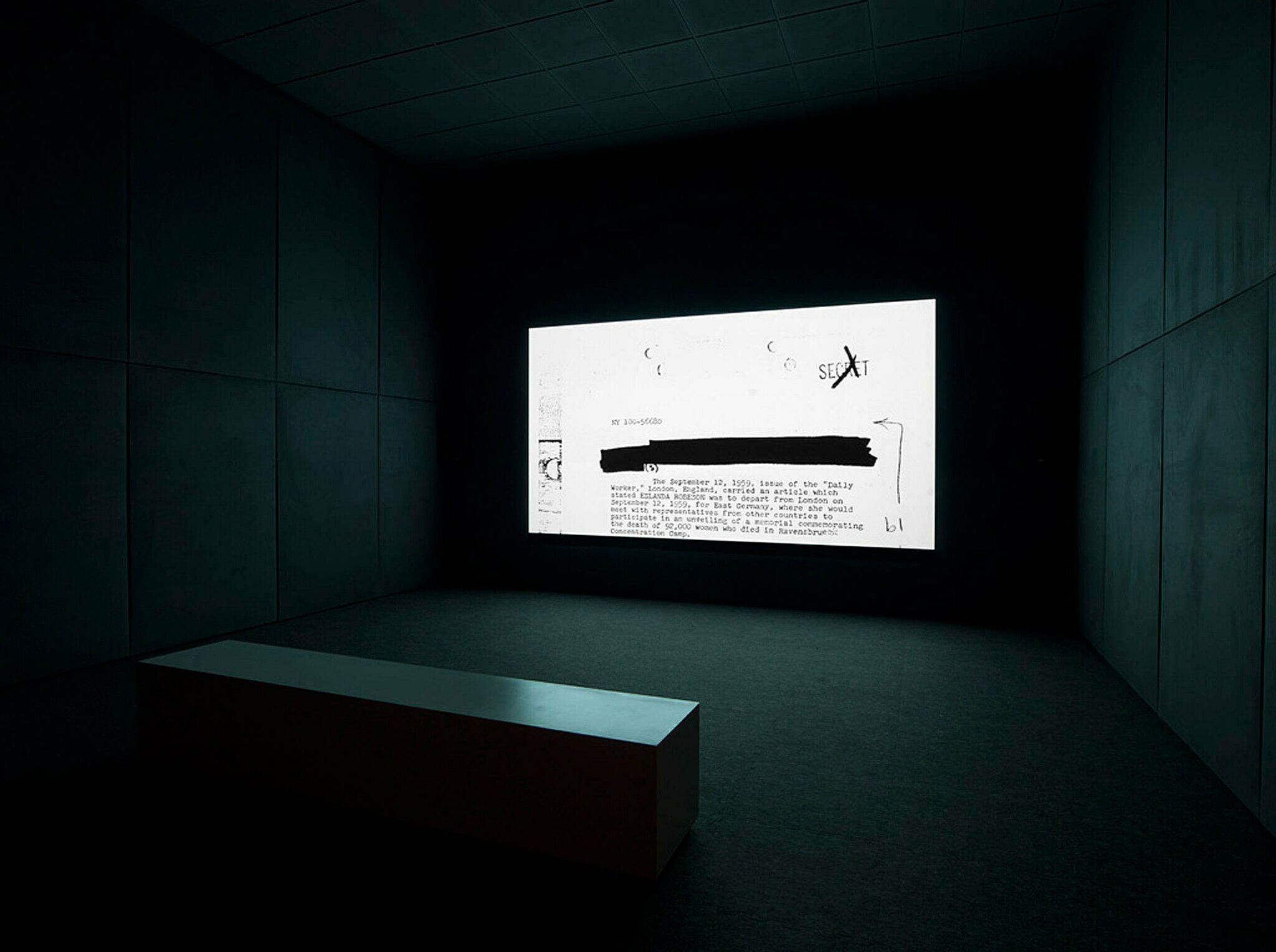 A projection of a work by Steve McQueen. A typed document flickers on the screen in a dark gallery