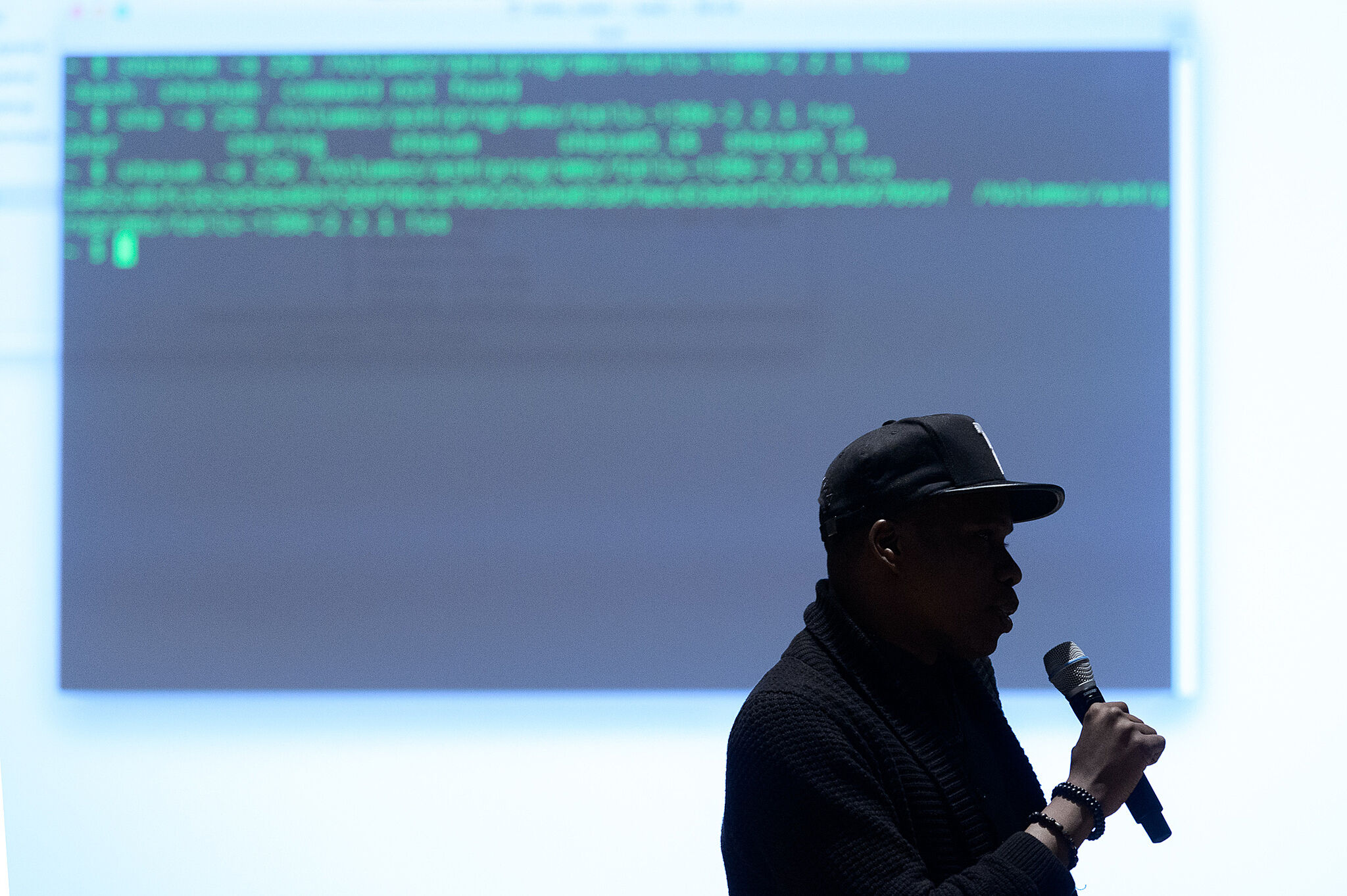 Matthew Mitchell leads a workshop in front of a projector displaying code