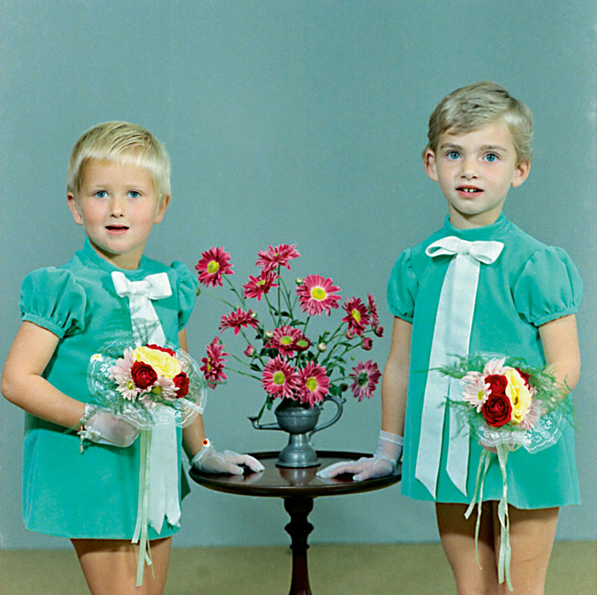 Wayne Koestenbaum's image of two children posing for a portrait. Each holds a bright bouquet of flowers.