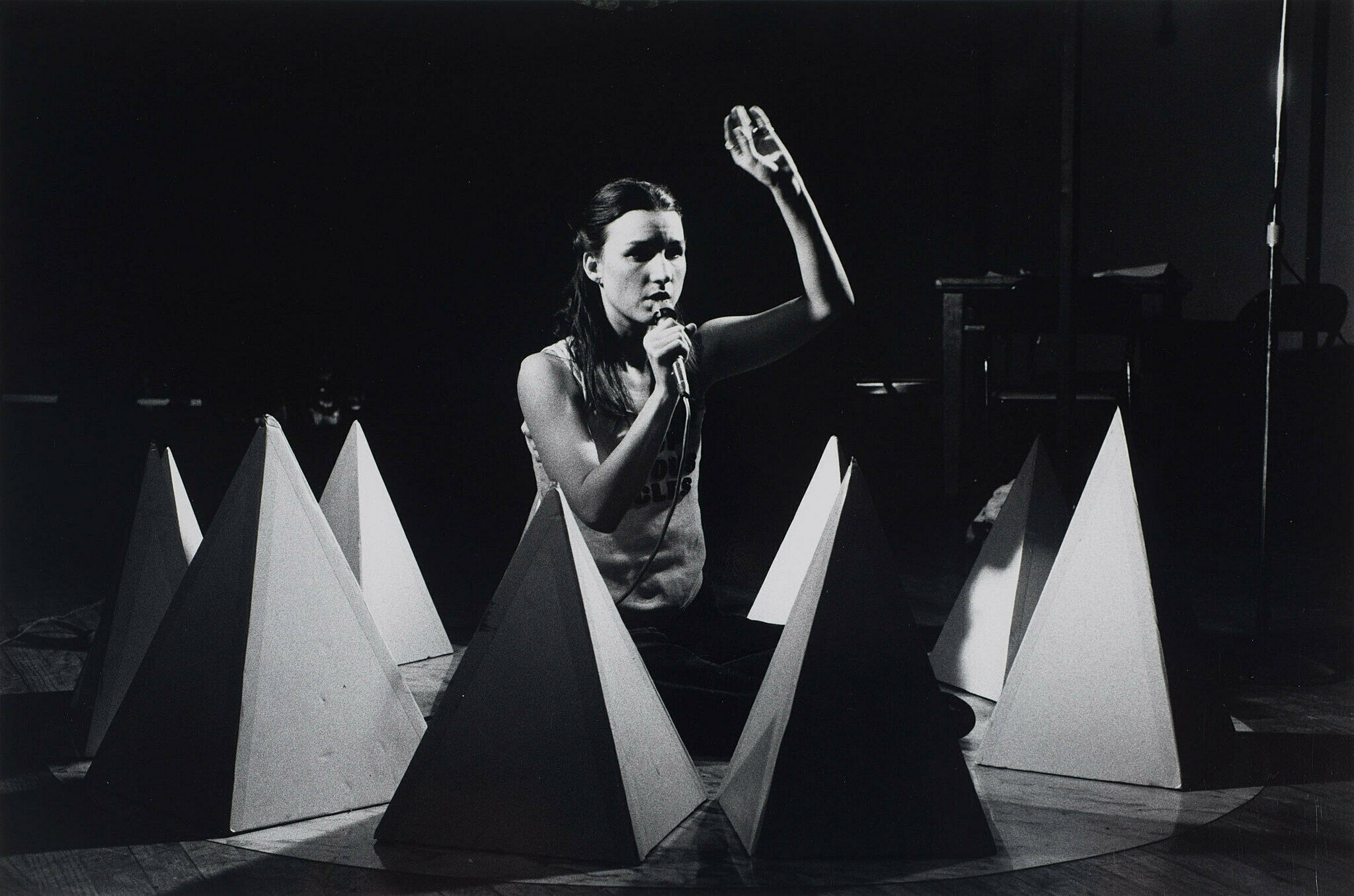 A woman kneels on a stage surrounded by sculptural objects.