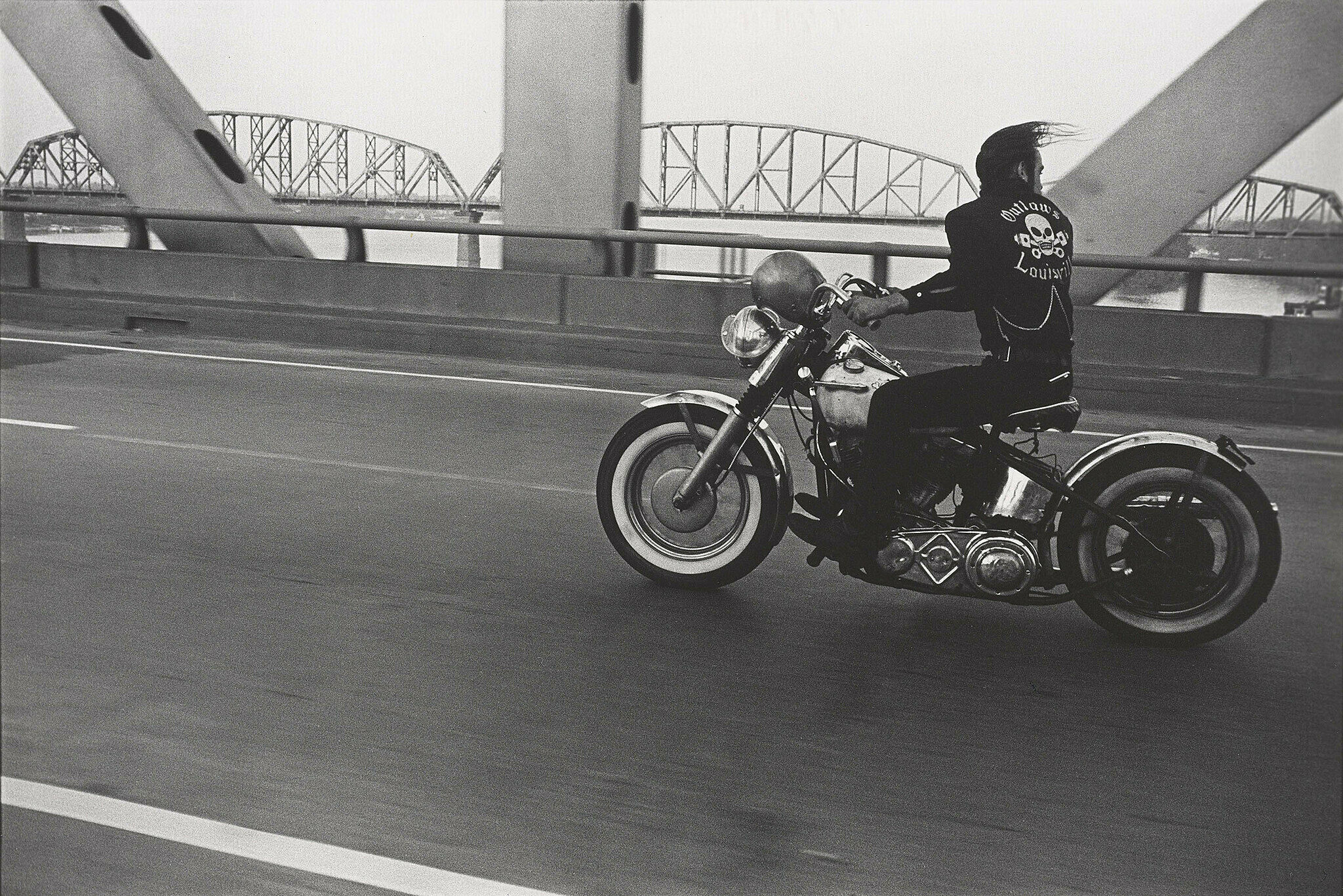 A work by Danny Lyon. A man driving a motorcycle across a bridge