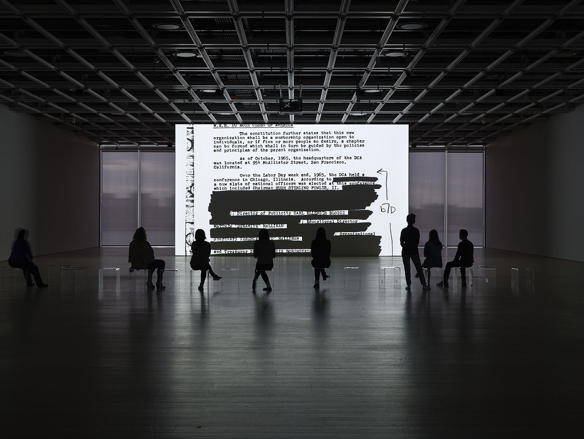 People sit and stand in a dark room with a screen displaying a document.