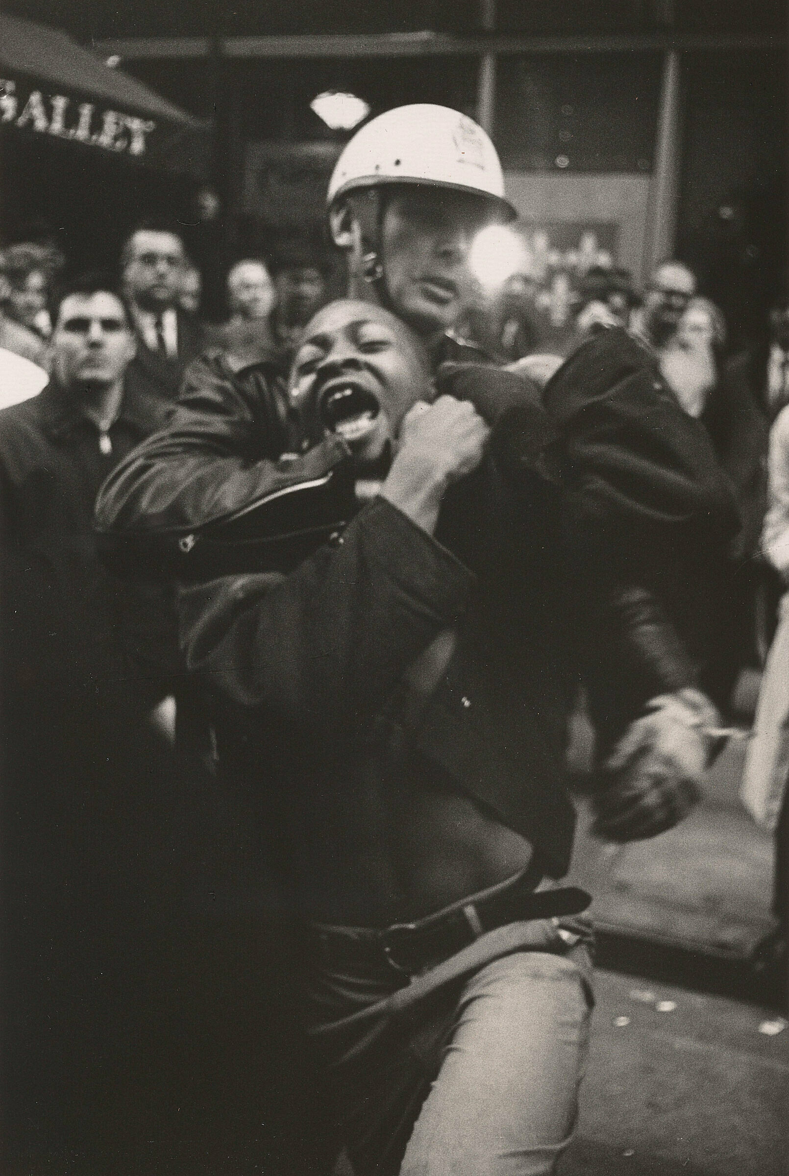A work by Danny Lyon. A man is arrested by a police officer