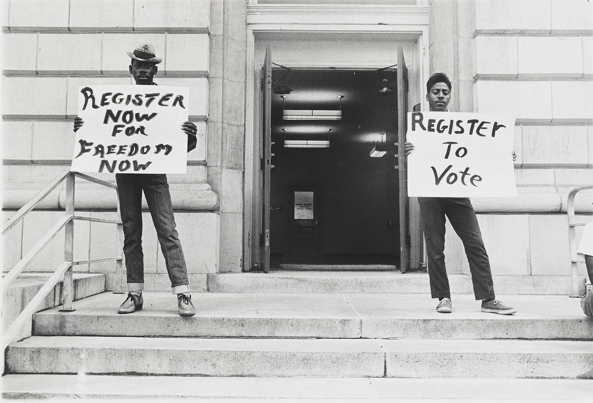 """Two people holding signs that say """"Register now for freedom now"""" and """"Register to vote"""""""