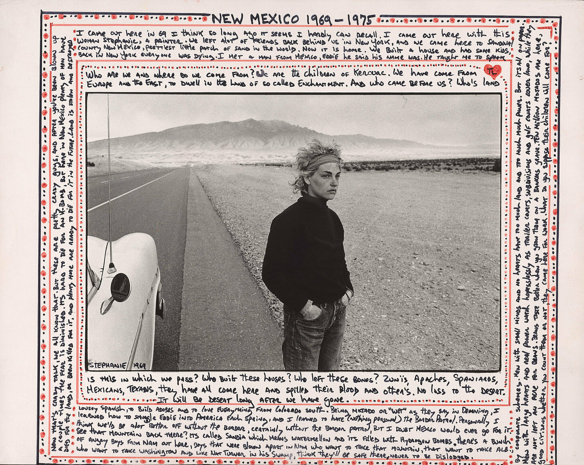 A work by Danny Lyon. A woman stands near a car on a highway in the desert. Writings decorate the border of the image
