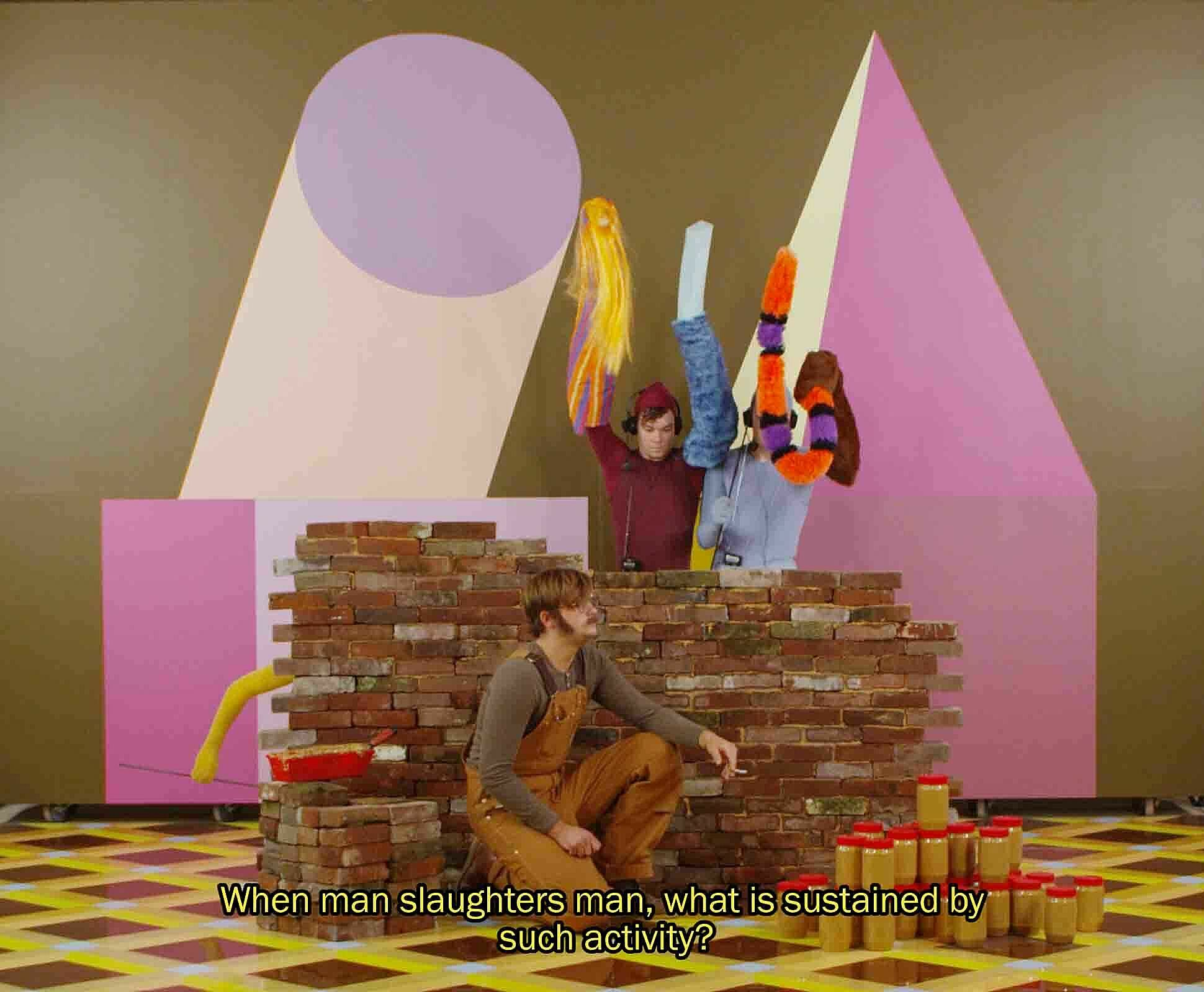 A still from a film work by Alex Da Corte. Three figures stage a puppet show in a fantasy landscape