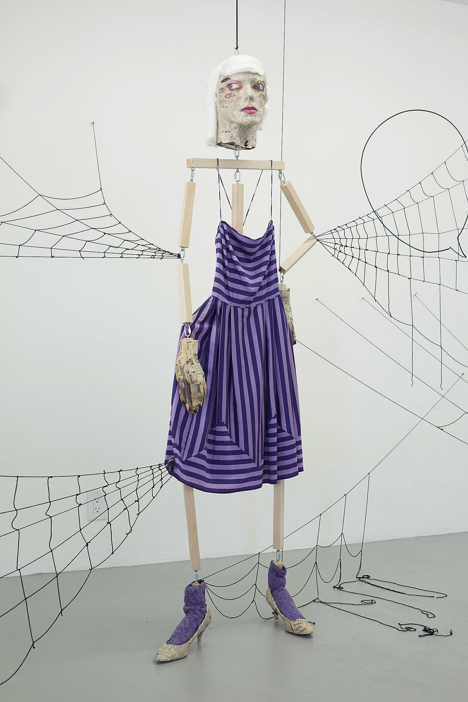 Figure of a woman in a purple striped dress with spider webs trailing off of her limbs.