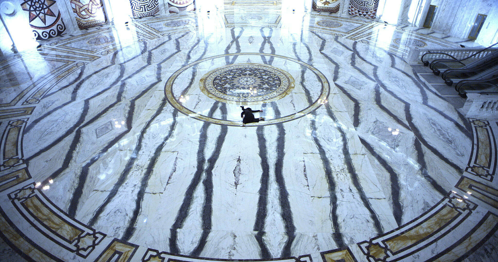 A video still by Sophia Al Maria. A view of a dark figure laying on the floor of a large, marbled hall.