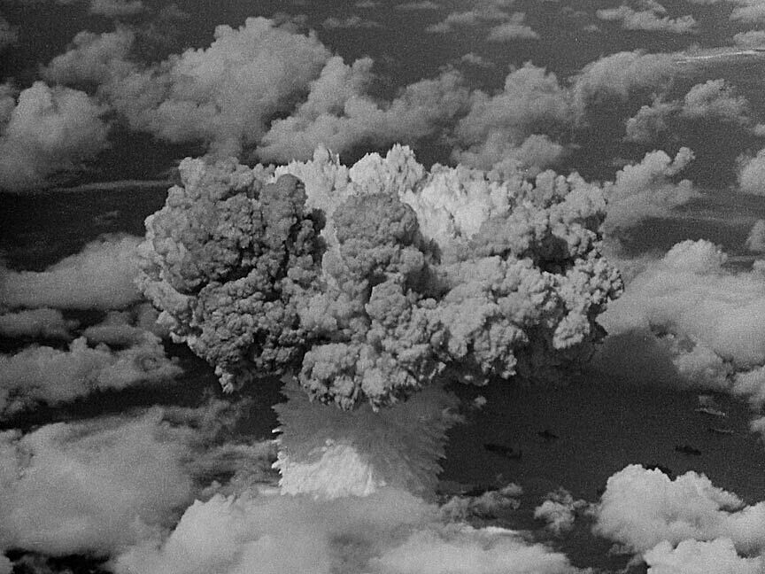 A still of a video work by Bruce Connor. A large mushroom cloud erupts in a cloudy sky