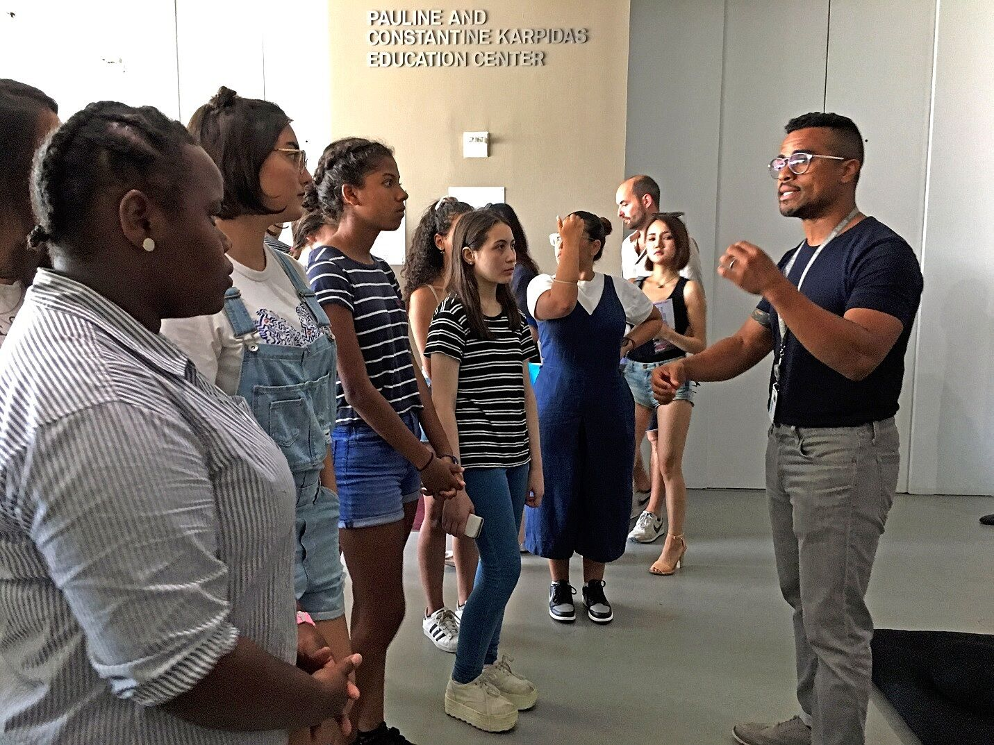 man explaining the museum exhibit to group of students