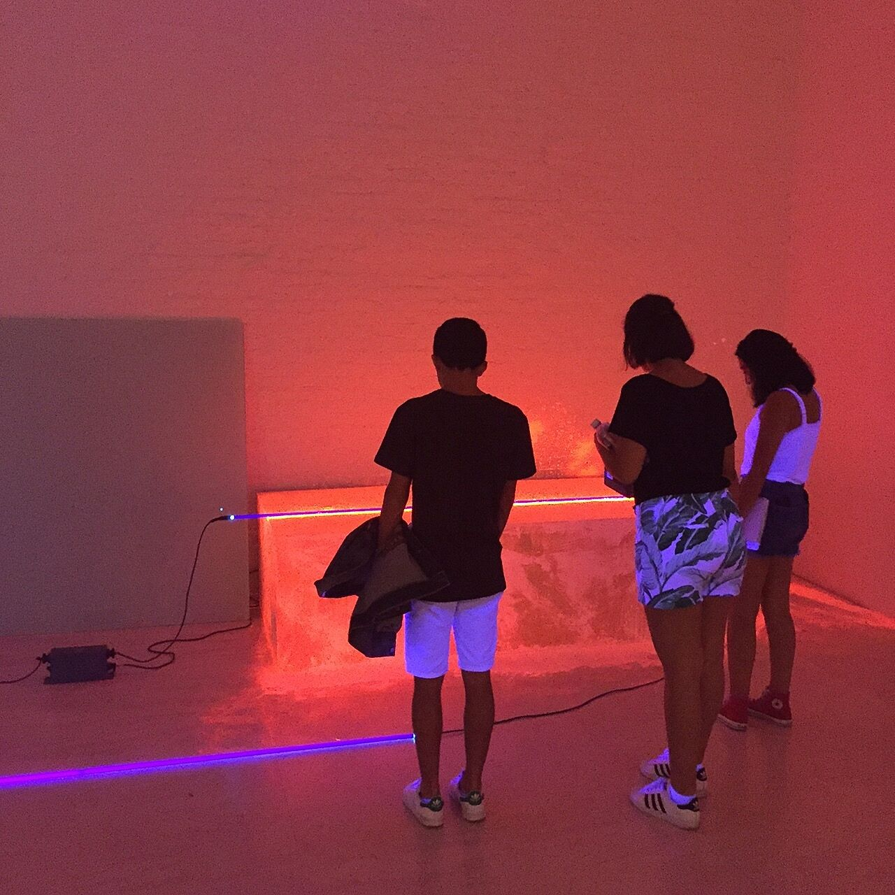 students in a room of neon light and installation