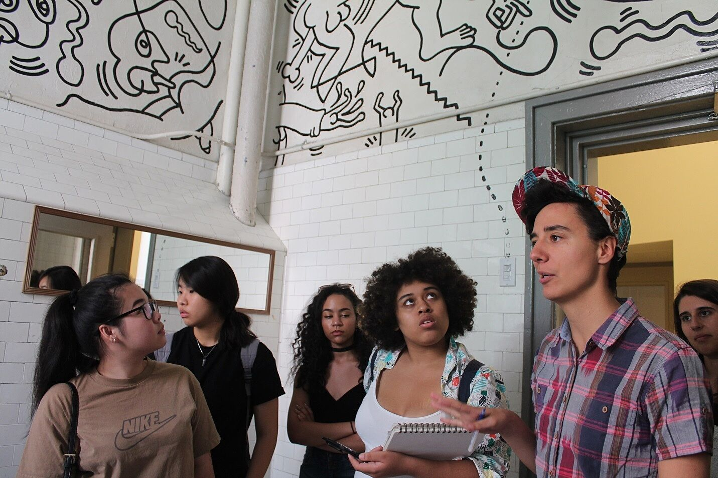 students talking in a room with a mural in it