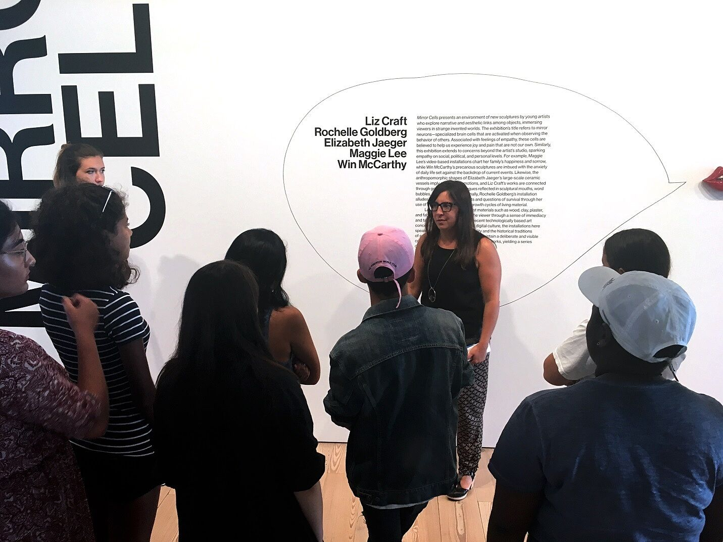 woman talking to teens in front of exhibition wall