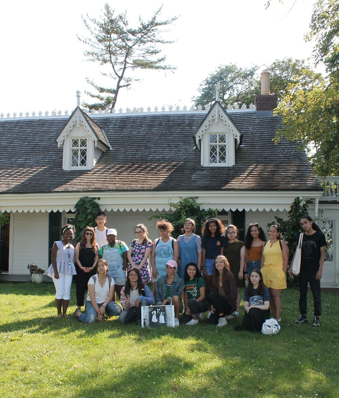 Students take picture in-front of artist's house.